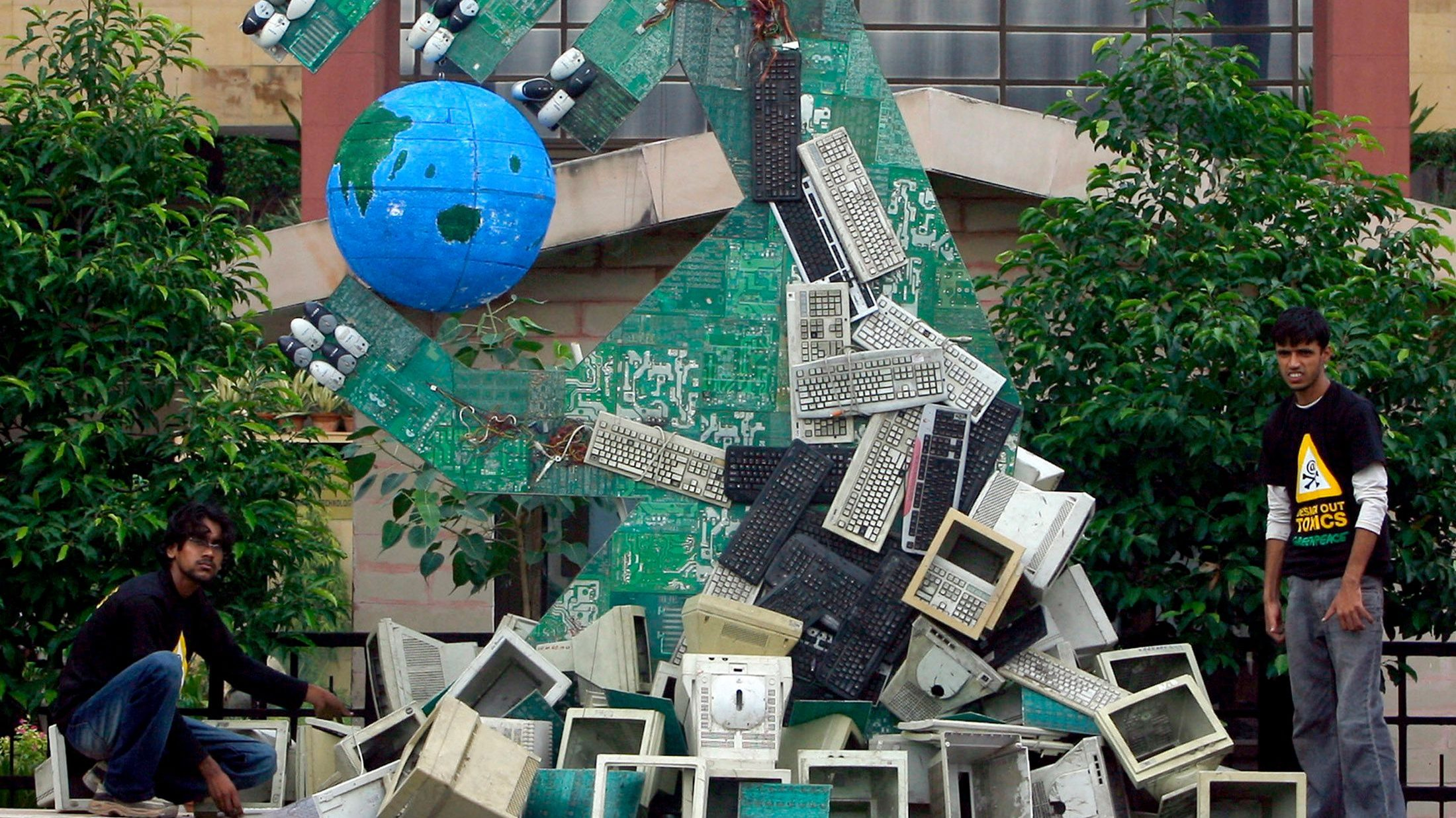 Greenpeace activists set up an art installation made of dismantled computers to send a message on hazardous electronic waste during a protest in front of the office of Indian Ministry of Information Technology in New Delhi August 20, 2007. REUTERS/Vijay Mathur (INDIA) - GM1DVYVJAVAA