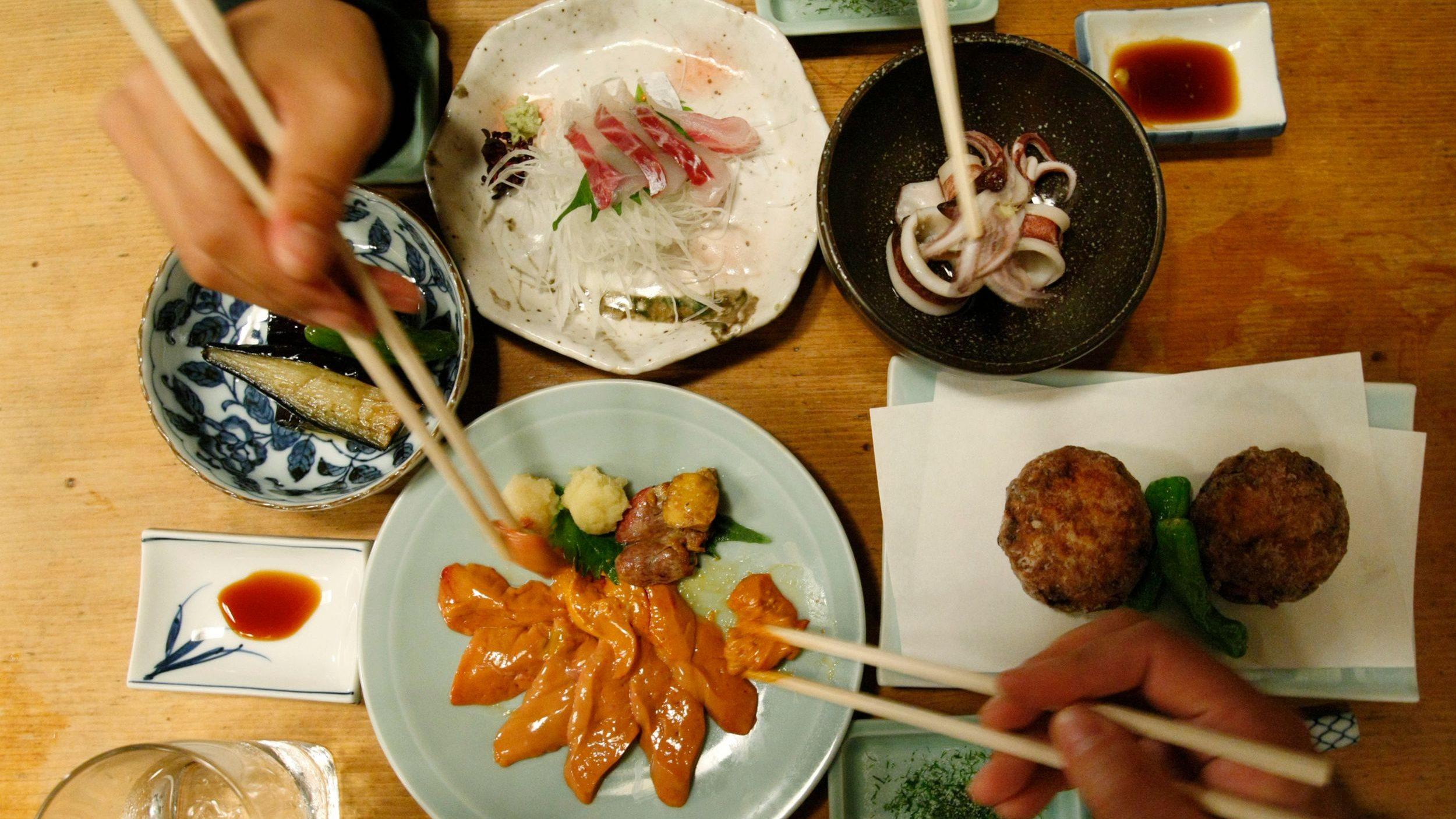 "People share dishes at a traditional Japanese ""Izakaya"" pub named Saiki in Tokyo"