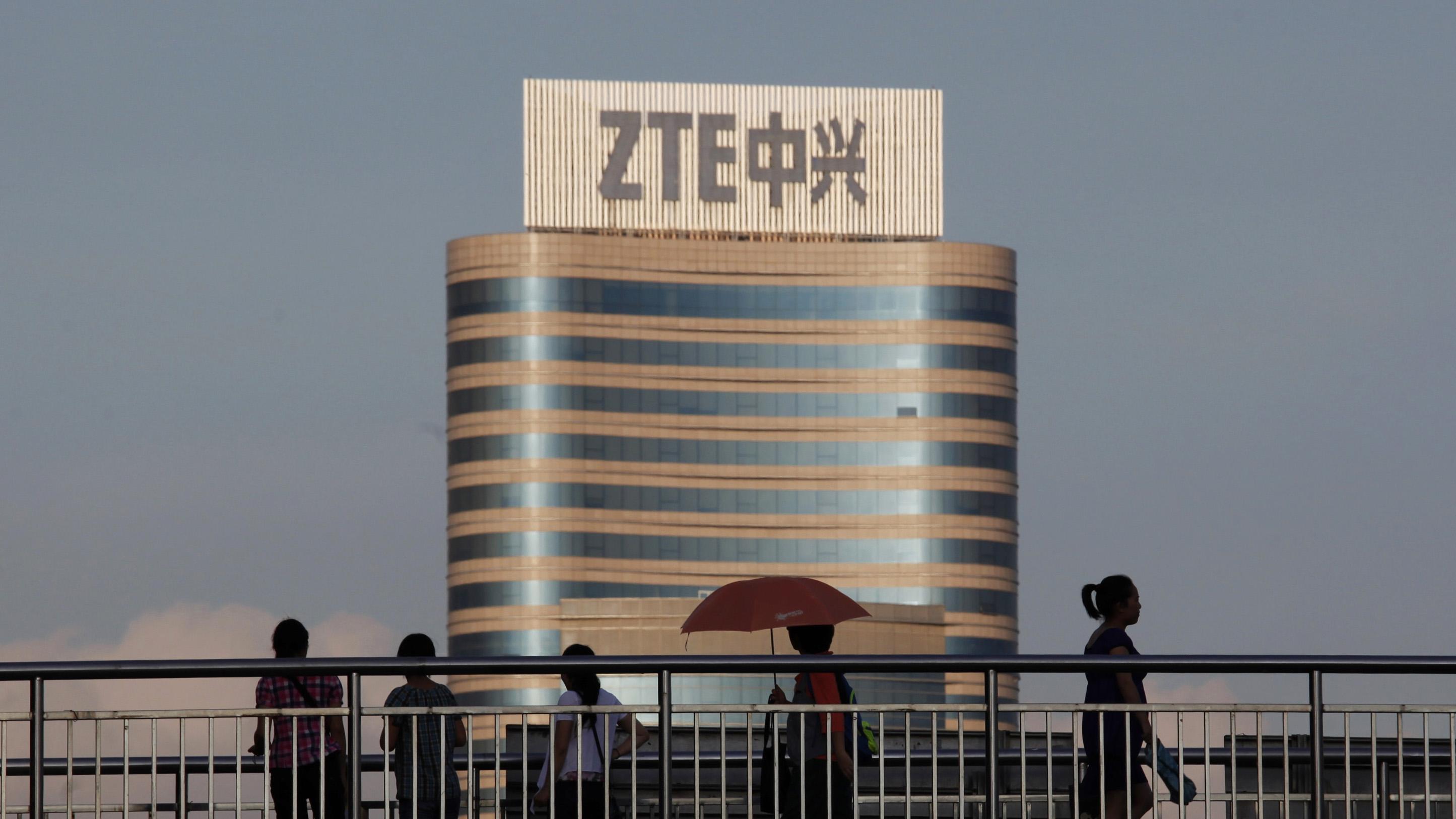 Passers by walk along a footbridge in front of the ZTE building in Nanshan Hi-Tech Industrial Estate in Shenzhen