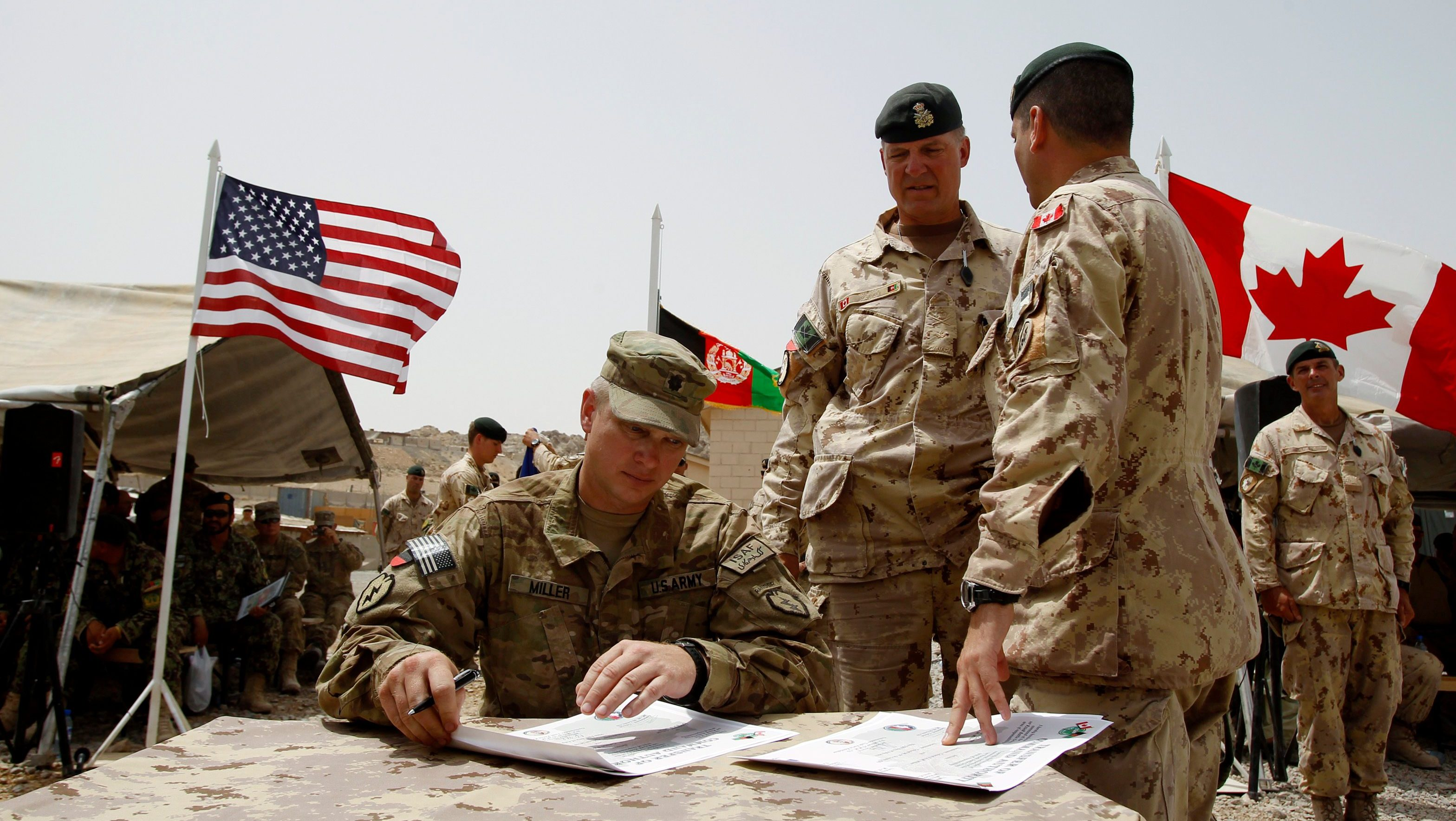 Canadian Brigadier-General Dean Milner (C) stands next to U.S. army Lieutenant Colonel Steve Miller as he signs a transfer of command document during a ceremony marking the handover of the Panjwai task force to American forces in forward fire base Masum Ghar Panjwai district in Kandahar province, southern Afghanistan, July 5, 2011. Canada is winding up combat operations in Afghanistan and all combat troops will leave by the end of July, after nearly ten years fighting in Afghanistan.  REUTERS/Baz Ratner (AFGHANISTAN  - Tags: MILITARY POLITICS CONFLICT) - GM1E7751CTW01