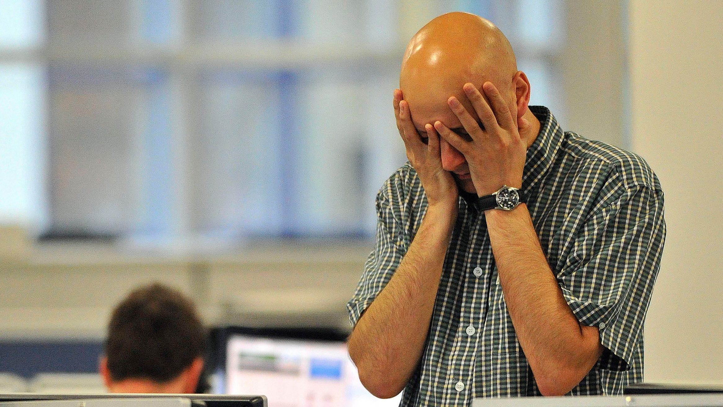A dealer reacts on the trading floor of IG Index in the City of London August 11, 2011.
