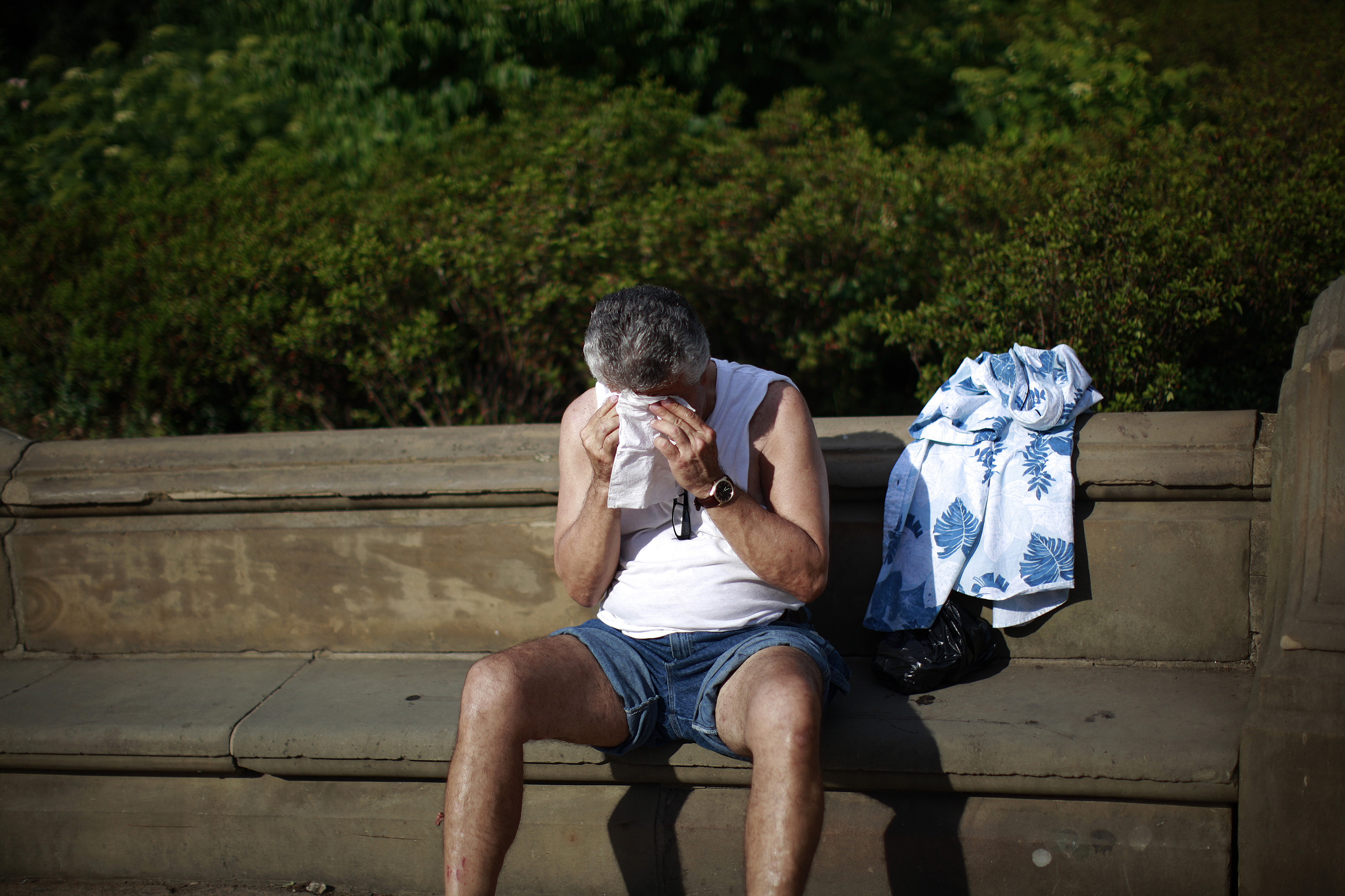 A man wipes his forehead while sitting in Central Park in New York