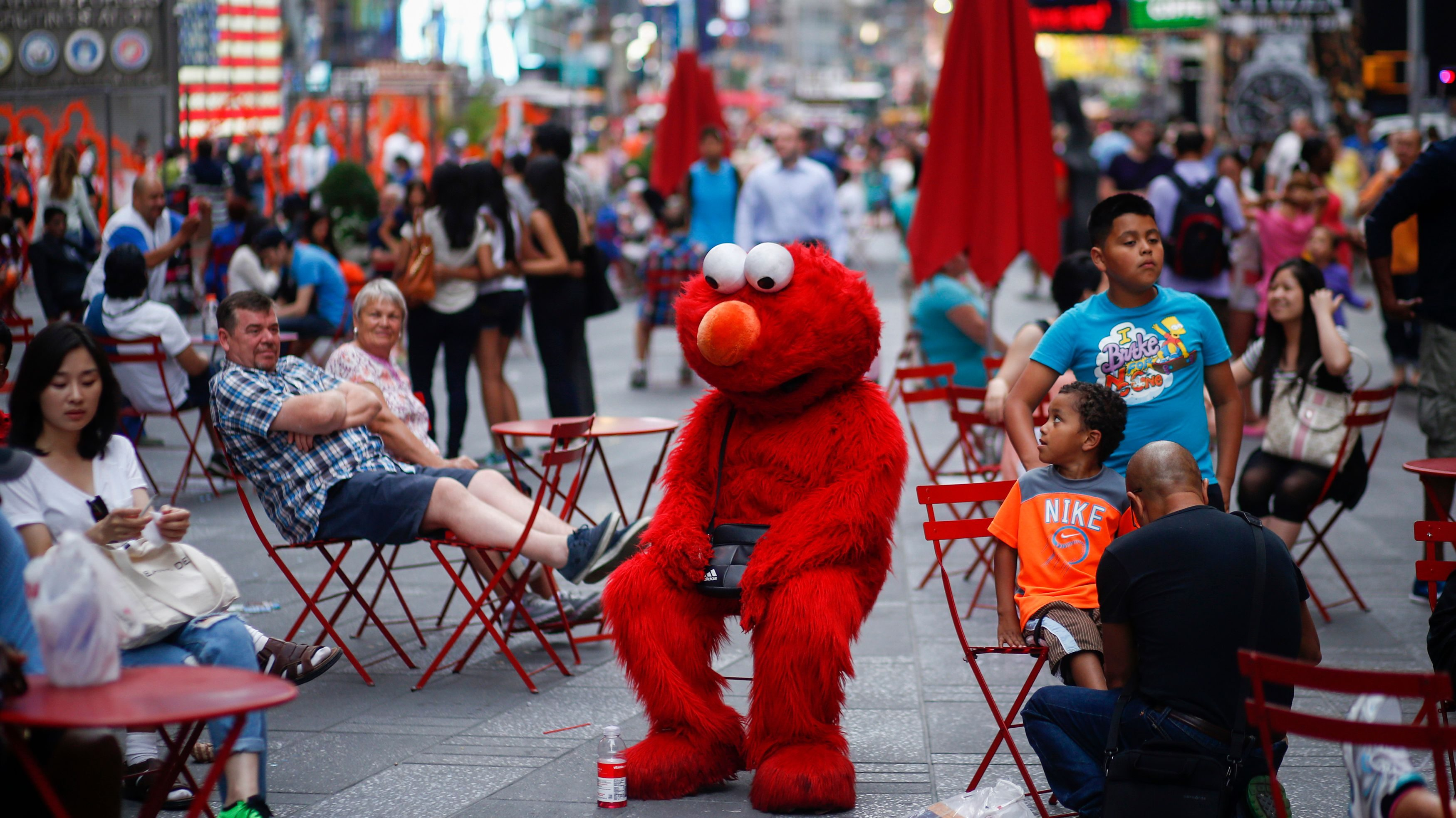 Jorge, an immigrant from Mexico, dressed as the Sesame Street character Elmo rests in Times Square, New York