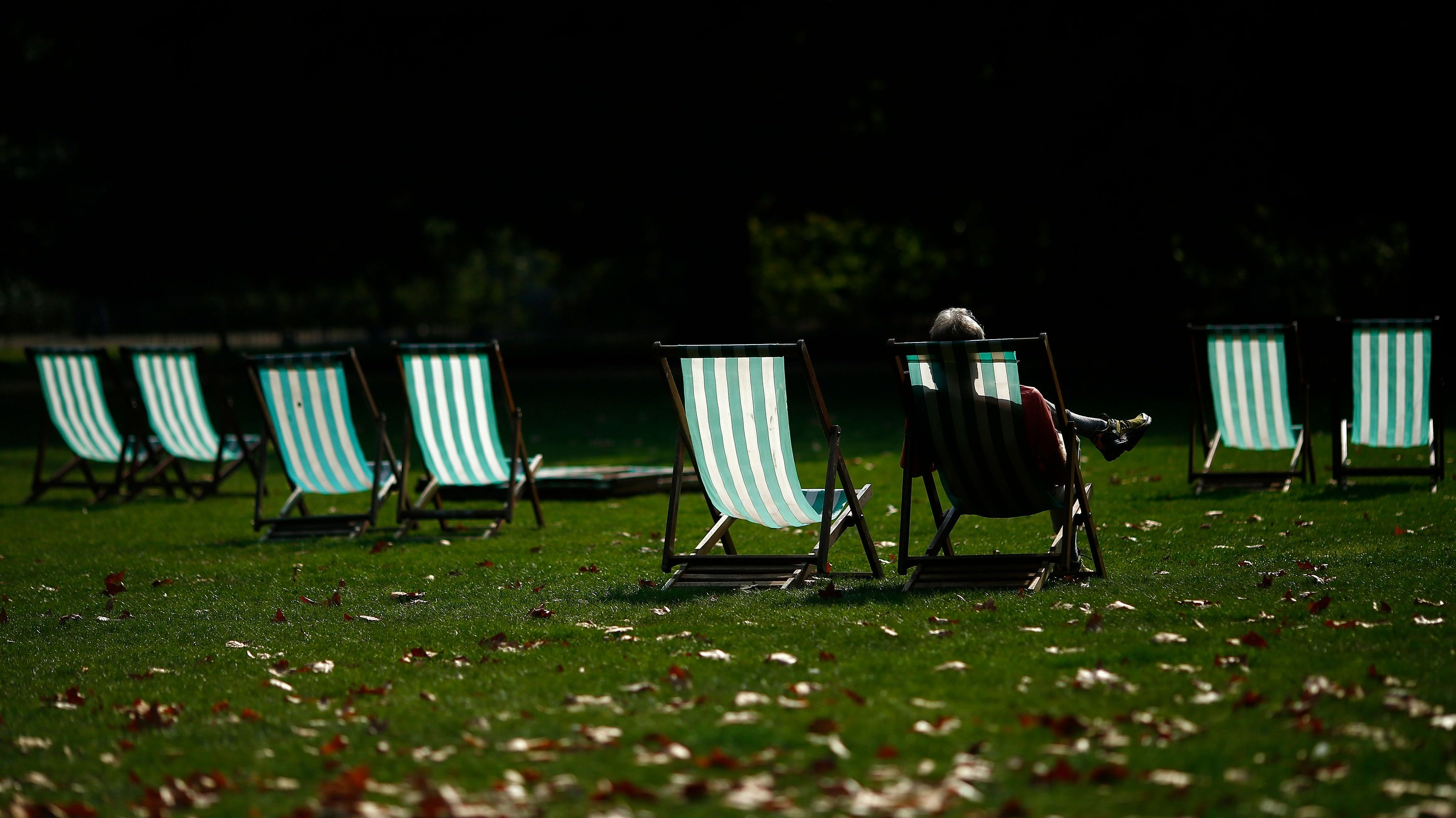 A visitor enjoys the autumn sunshine on a deck chair in St James Park, central London
