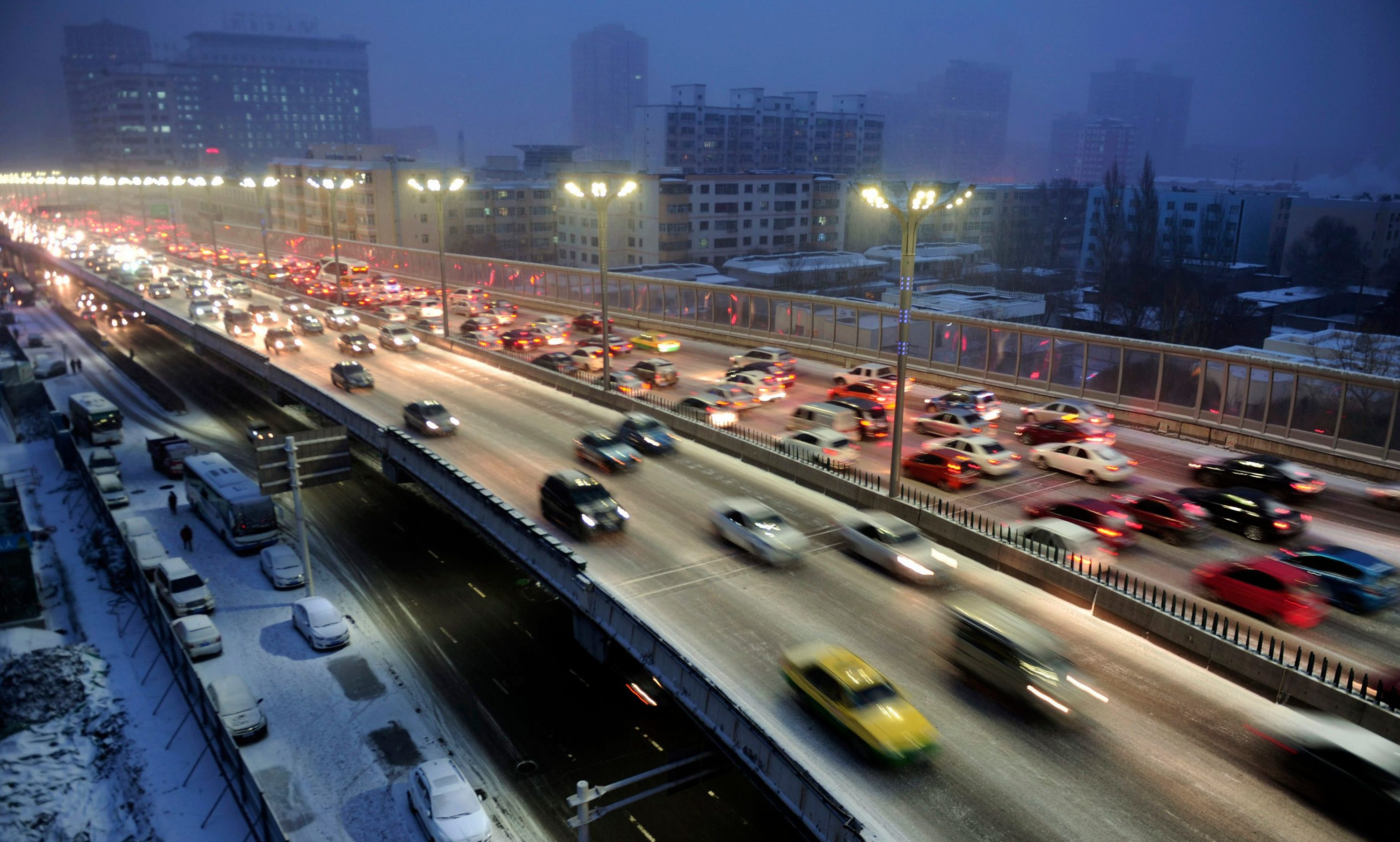 Cars drive along a bridge after snowfall in Urumqi, Xinjiang Autonomous region, November 28, 2014. Picture taken November 28, 2014. REUTERS/Stringer (CHINA - Tags: ENVIRONMENT TRANSPORT) CHINA OUT. NO COMMERCIAL OR EDITORIAL SALES IN CHINA - GM1EABT1HKC01