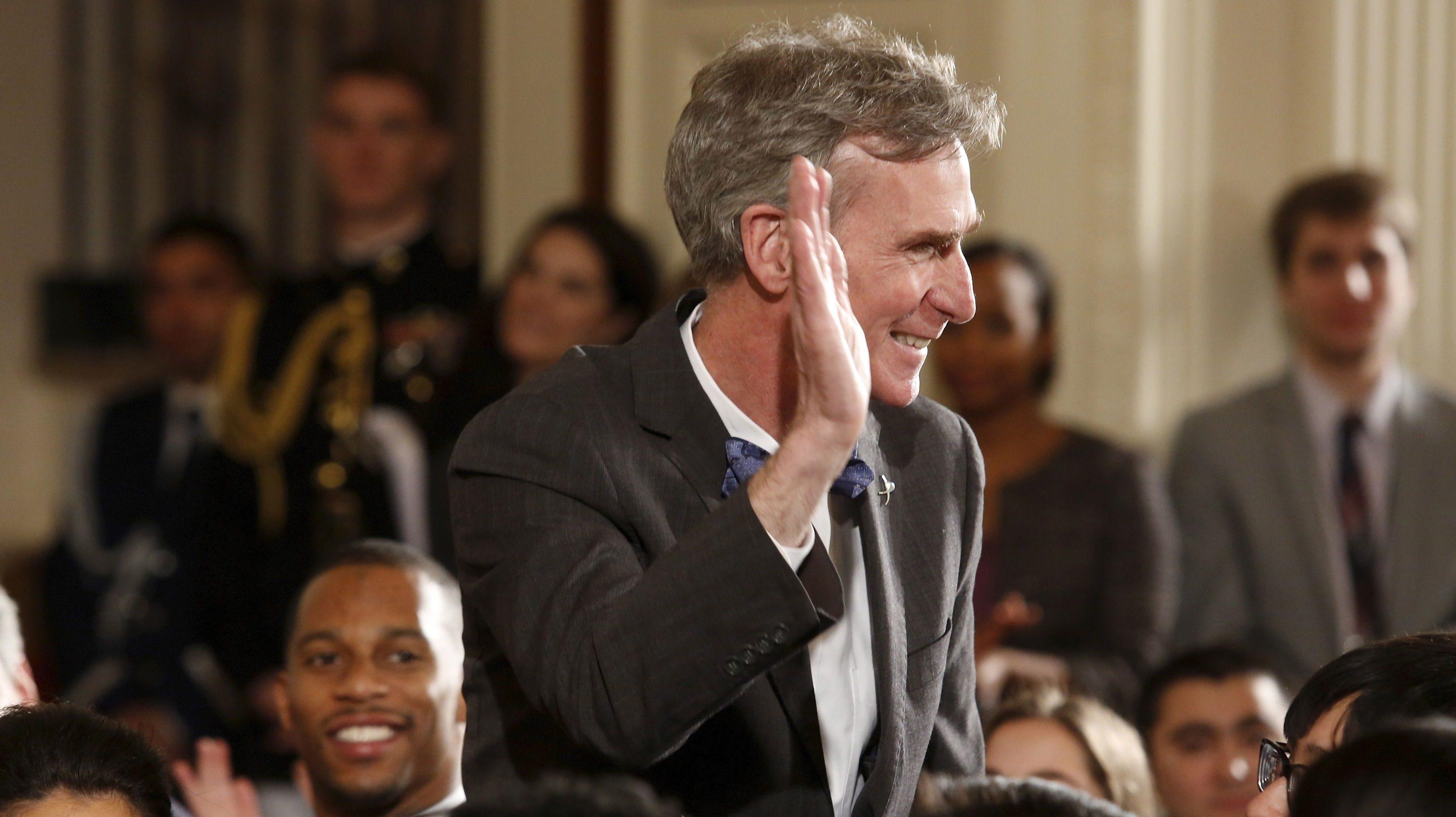 Bill Nye waving toward others.
