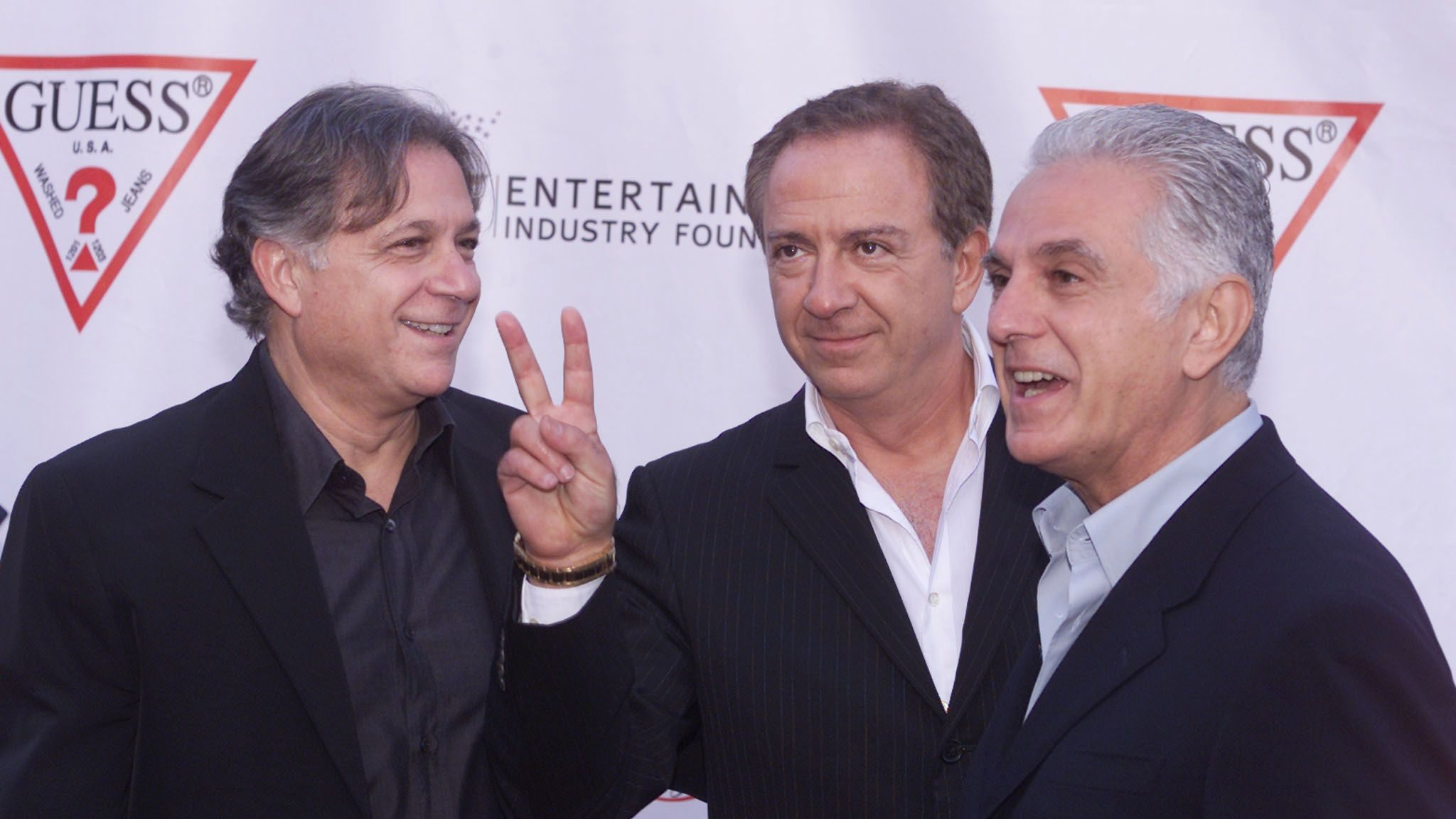 Armand (L) Paul (C) and Maurice Marciano, founders of the GUESS? clothing line pose as they arrive at their company's 20th anniversary party in Los Angeles May 9, 2002. The brothers, originally from France, started the company in Los Angeles twenty years ago and sold their first order of 24 pairs of jeans to Bloomingdales. REUTERS/Fred Prouser REUTERS  FSP - RP3DRHZBCIAA
