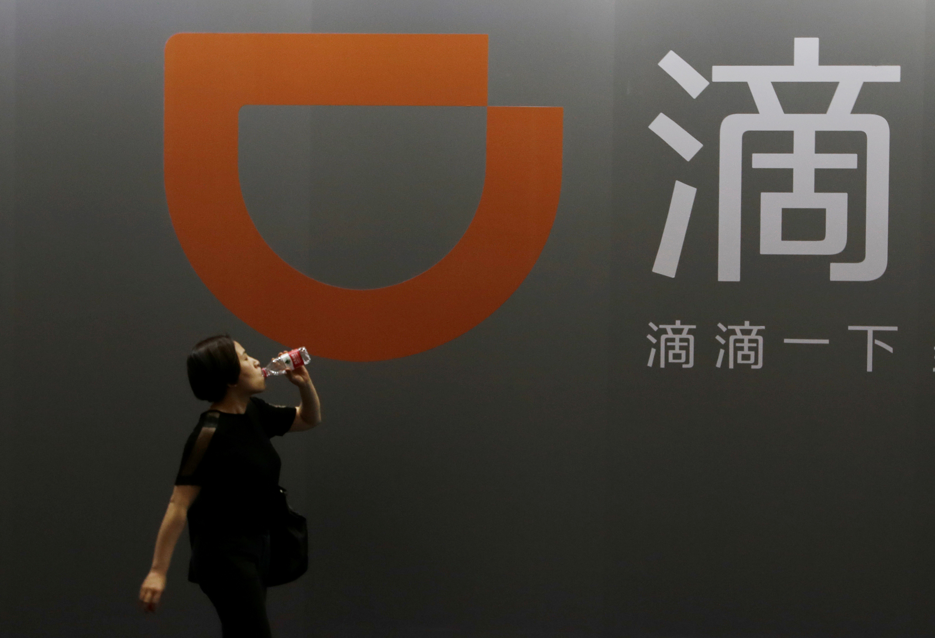 A woman walks past Didi Chuxing's booth at the Global Mobile Internet Conference (GMIC) 2017 in Beijing, China