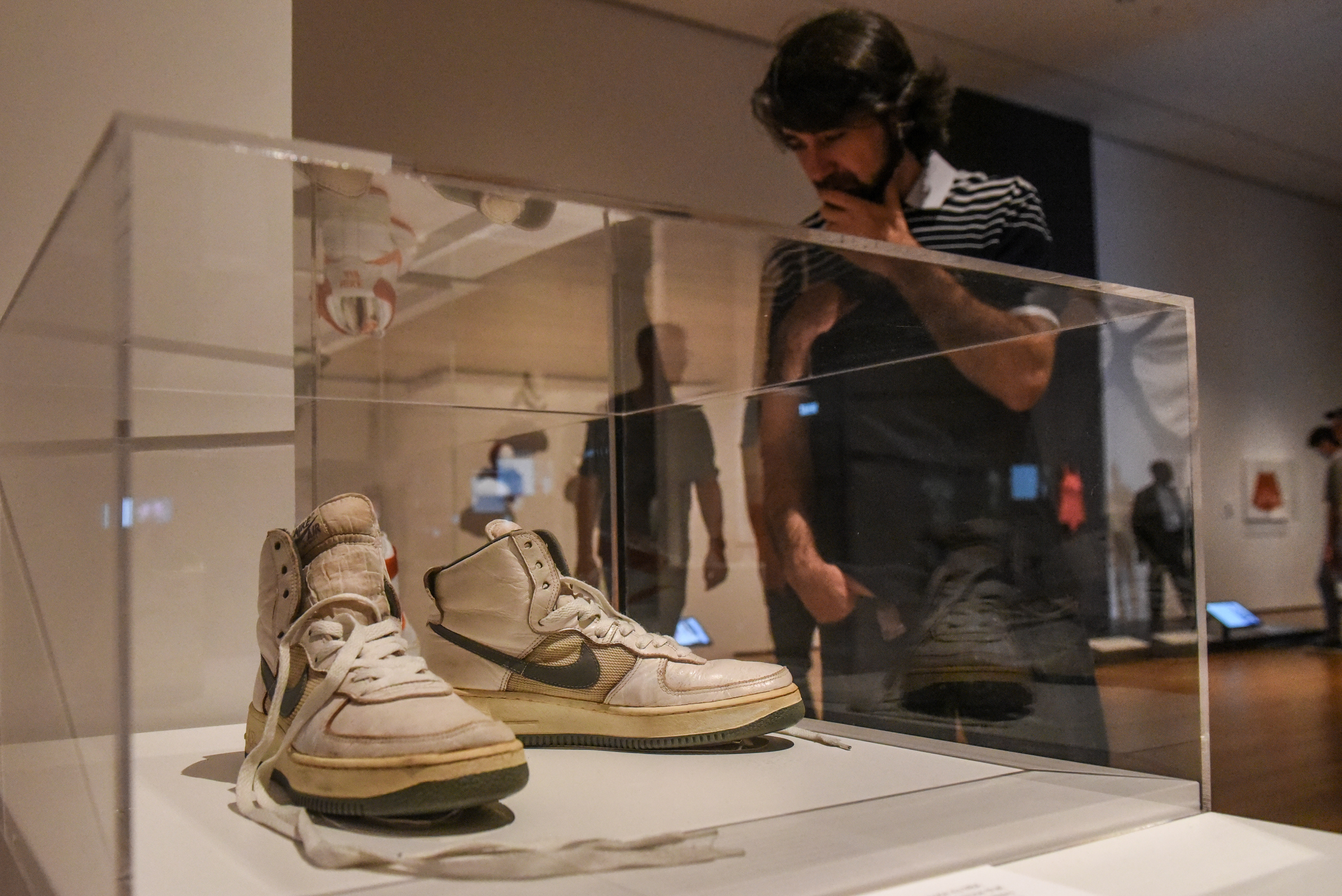 A person looks at a pair of sneakers on display at the Museum of Modern Art's exhibition called Items: Is Fashion Modern? in New York City, U.S. October 6, 2017. REUTERS/Stephanie Keith - RC1B5B88F7D0