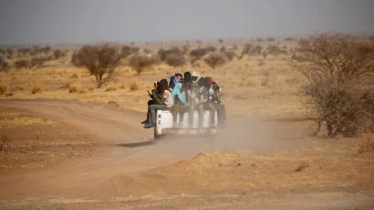 Migrants crossing the Sahara desert into Libya ride on the back of a pickup truck outside Agadez