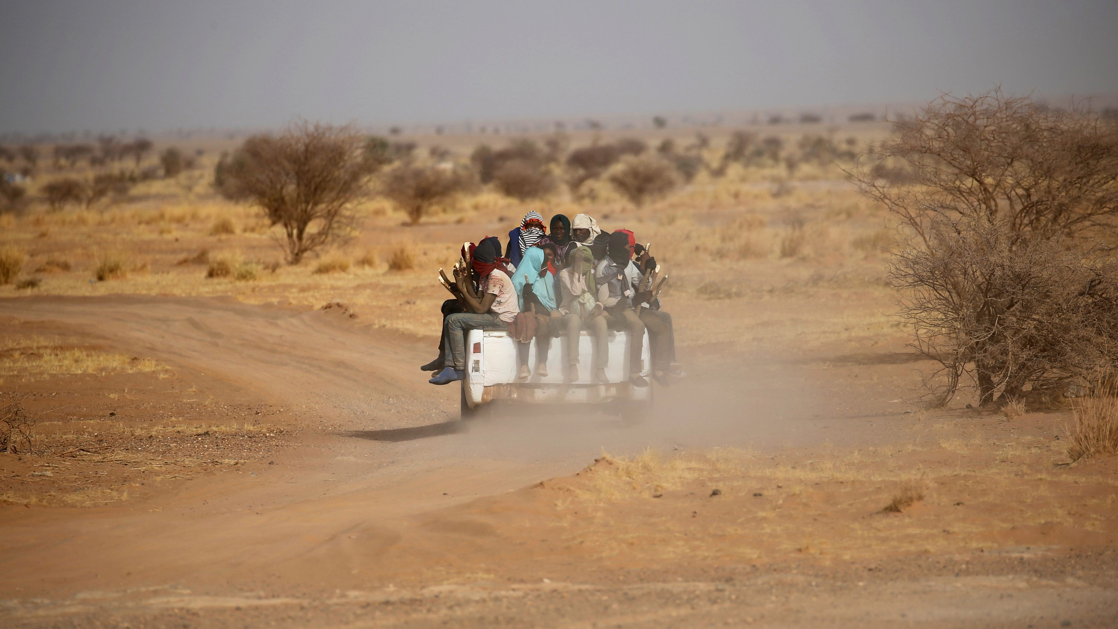Migrants crossing the Sahara desert into Libya ride on the back of a pickup truck outside Agadez, Niger, May 9, 2016. Picture taken May 9, 2016.