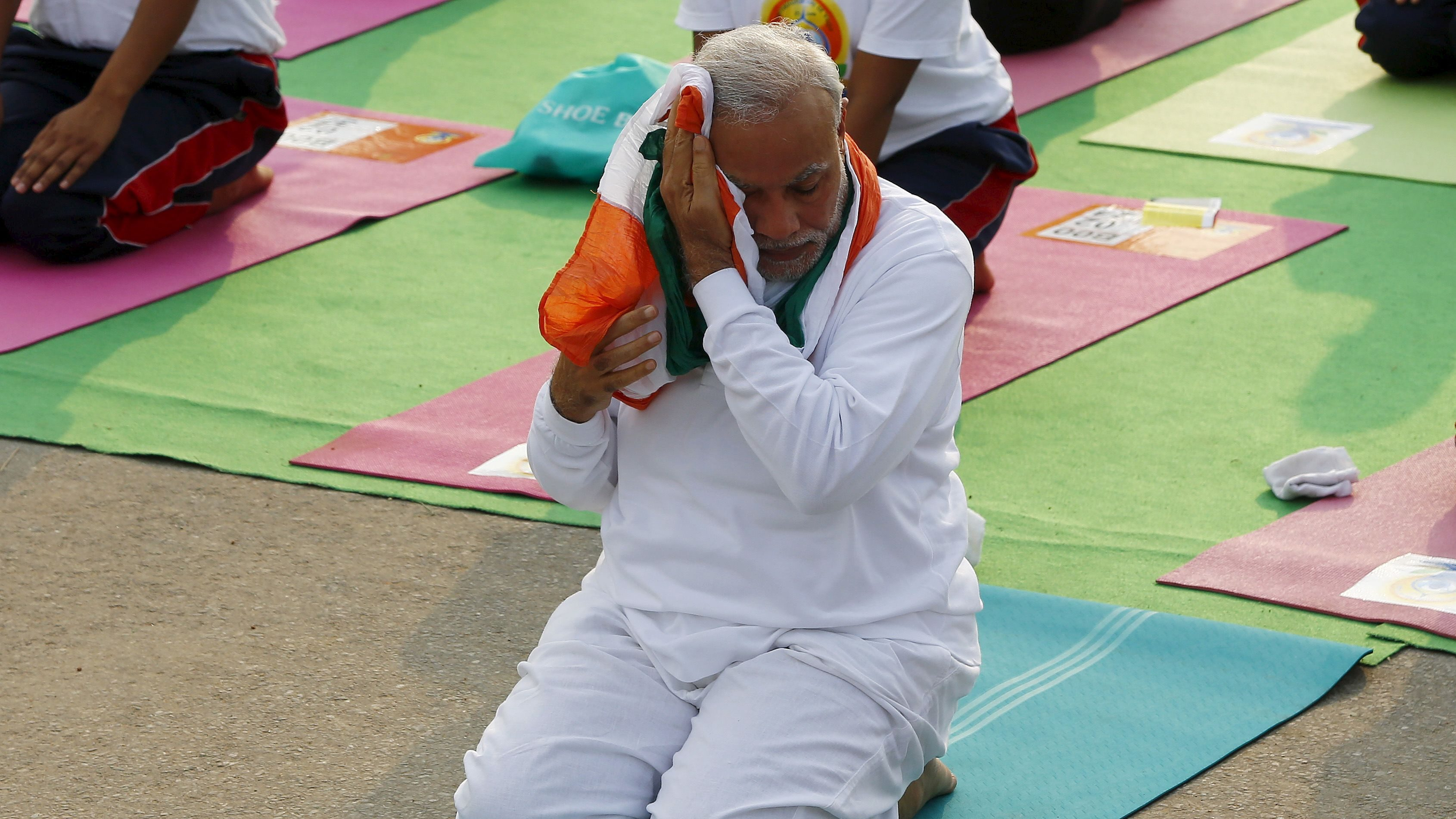India's Prime Minister Narendra Modi wipes his perspiration with a scarf as he performs yoga to mark the International Day of Yoga, in New Delhi, India, June 21, 2015. Modi led tens of thousands of people in the yoga session in the centre of the capital on Sunday to showcase the country's signature cultural export, which has prompted criticism of fomenting social divisions at home.
