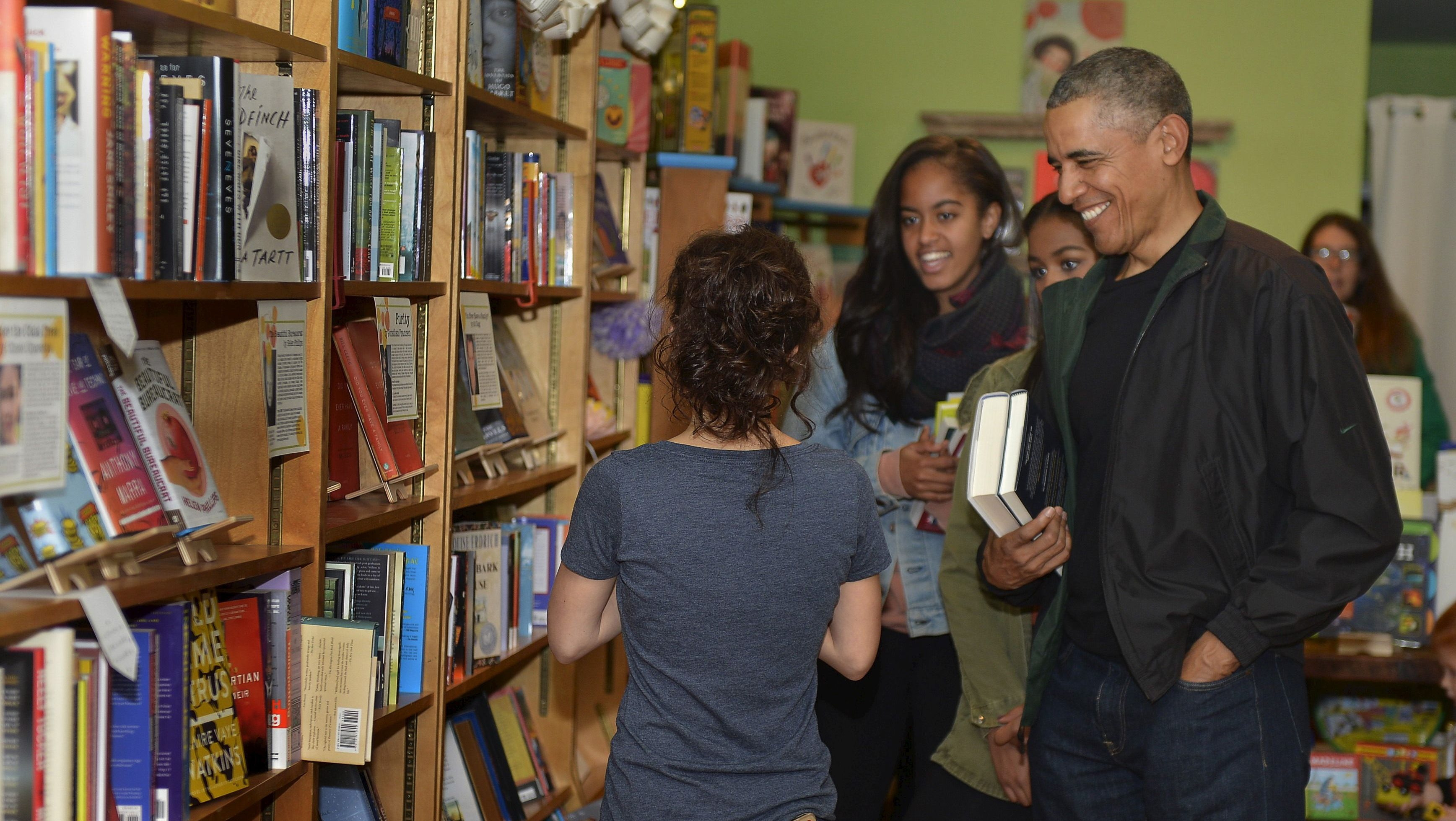 U.S. President Barack Obama (R) and his daughters Malia (C) and Sasha (partly hidden) interact with Upshur Street Books manager Anna Thorn as they buy books from the store in Washington, November 28, 2015. Today is Small Business Saturday, which was started to encourage shoppers to buy locally and from brick-and-mortar stores, and serves as a counterpoint to the traditionally busy shopping days of Black Friday and Cyber Monday after the Thanksgiving holiday.        REUTERS/Mike Theiler  - GF20000077754