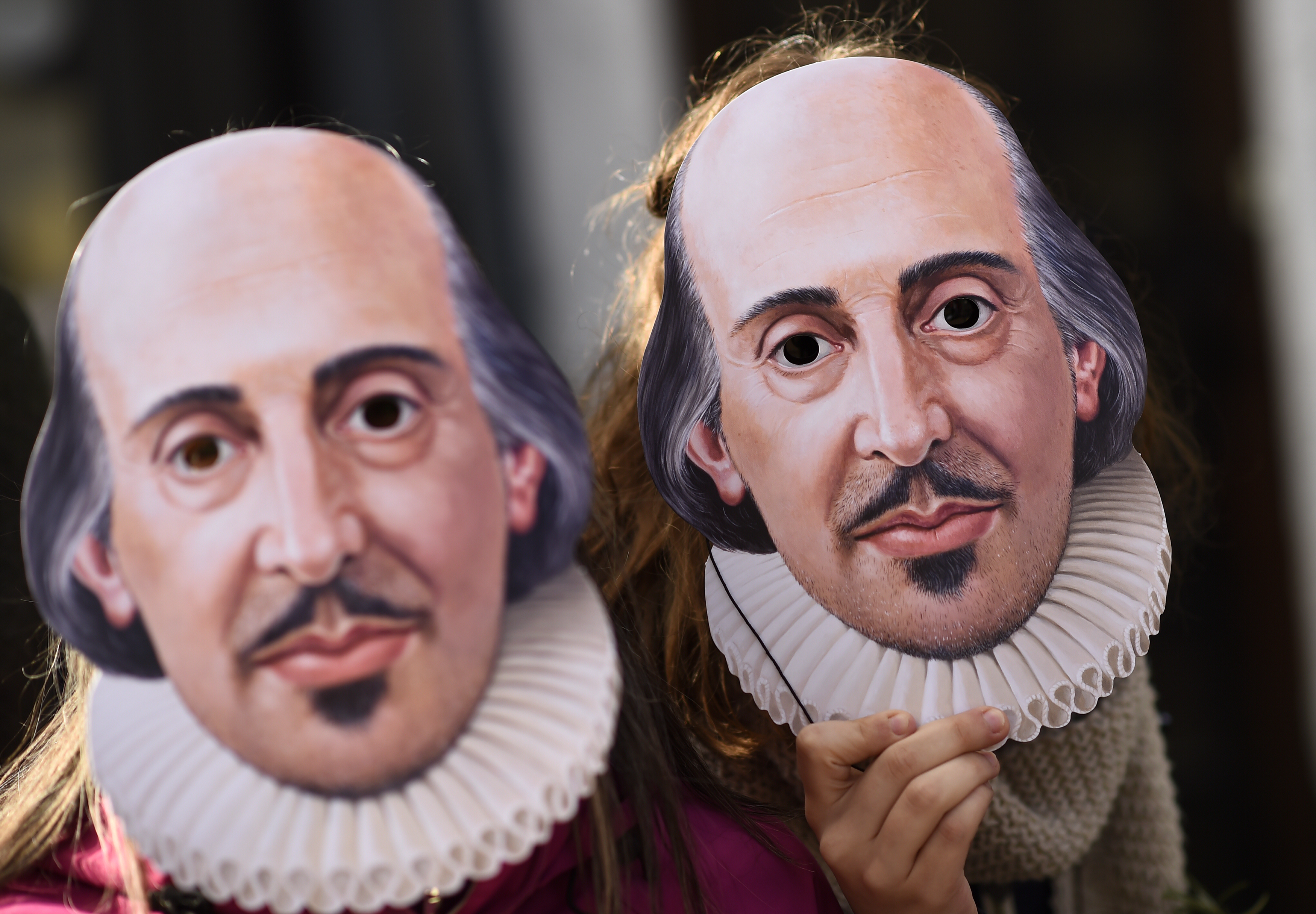 People hold up face masks with William Shakespeare's portrait during celebrations to mark the 400th anniversary of the playwright's death in the city of his birth, Stratford-Upon-Avon