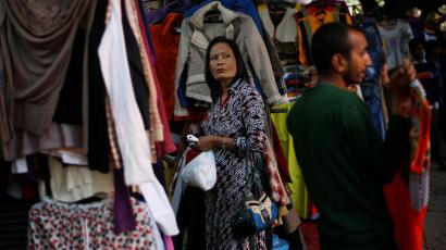 A woman buys clothes in a shop at a market in New Delhi