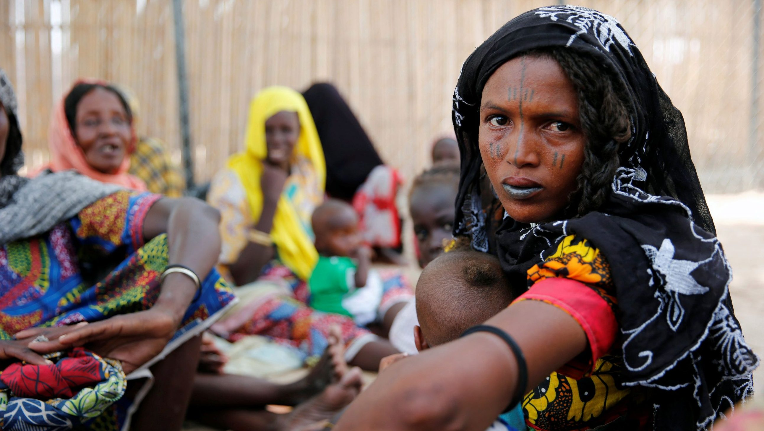 Woman sits outside a shed as she waits for food rations at IDP camp on the outskirts of Maiduguri