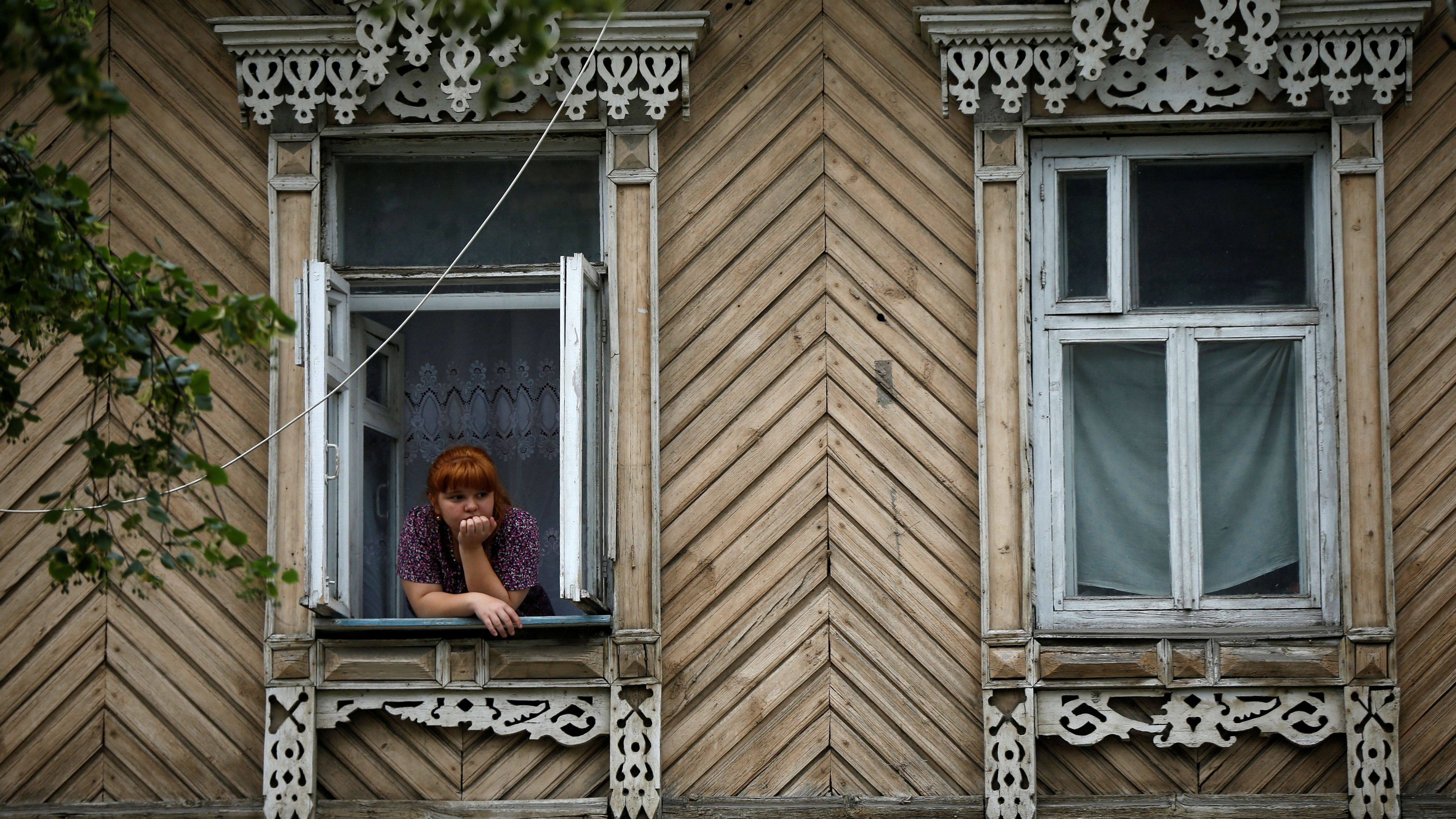 A woman looks out of window in Samara