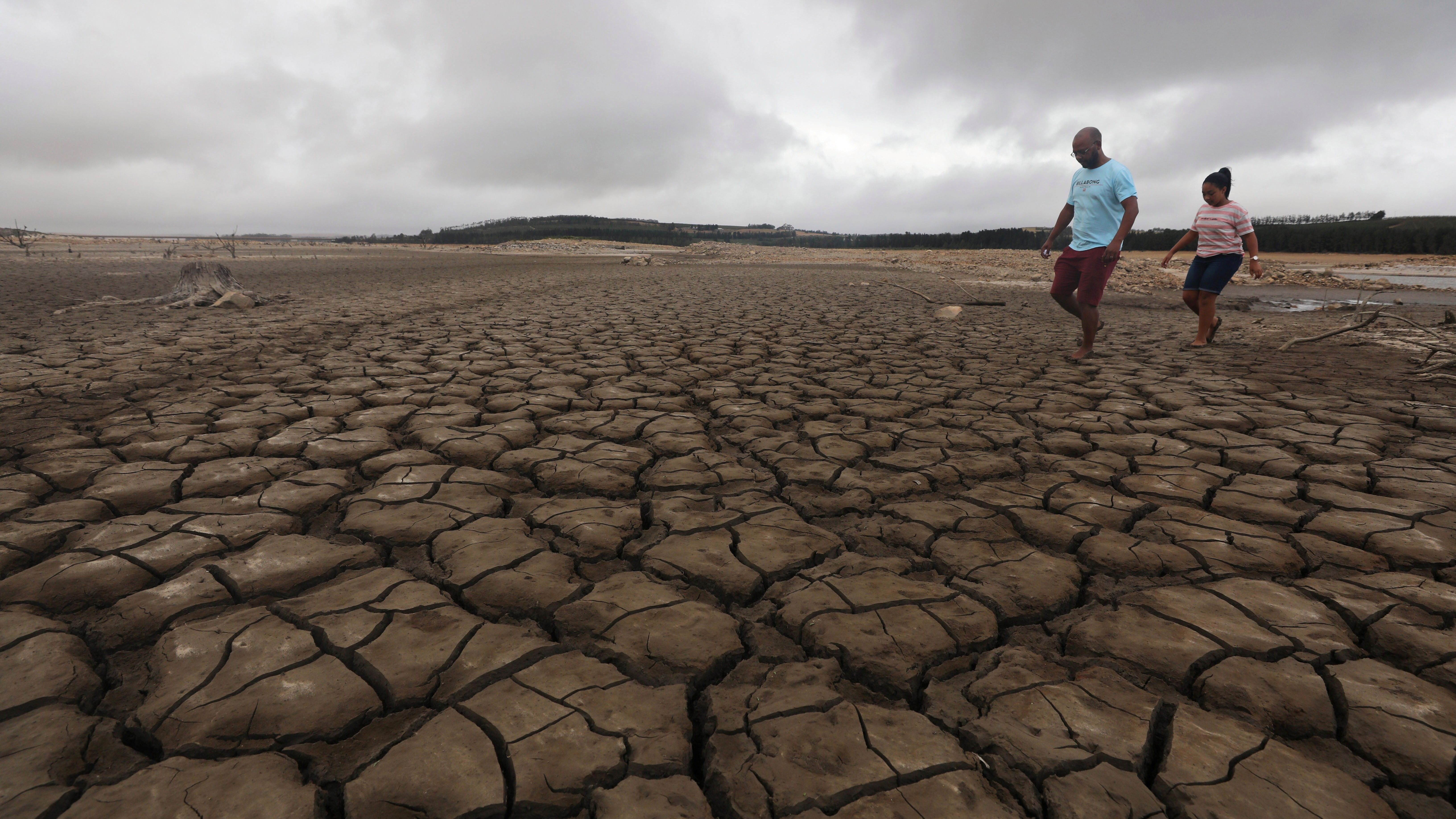 A family negotiates their way through caked mud around a dried up section of the Theewaterskloof dam near Cape Town