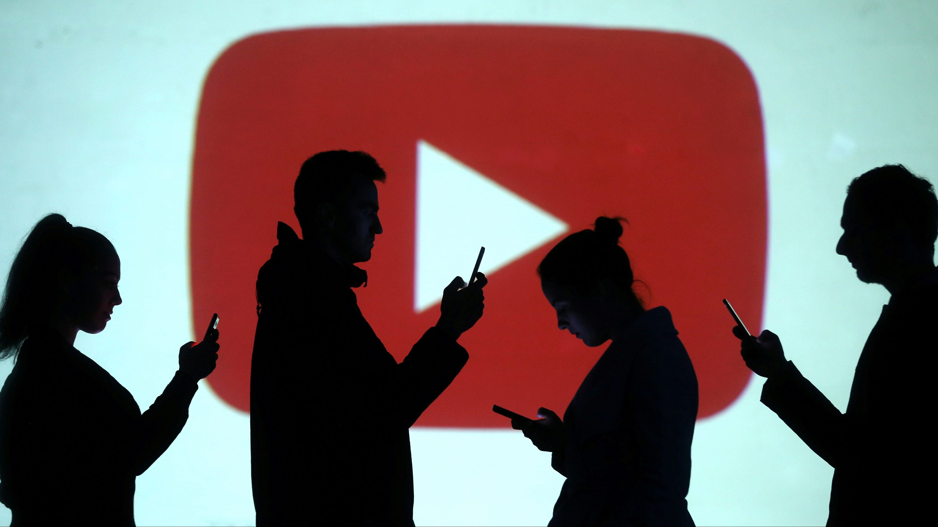Silhouettes of mobile users are seen next to a screen projection of Youtube logo in this picture illustration taken March 28, 2018.  REUTERS/Dado Ruvic/Illustration - RC1D24345500