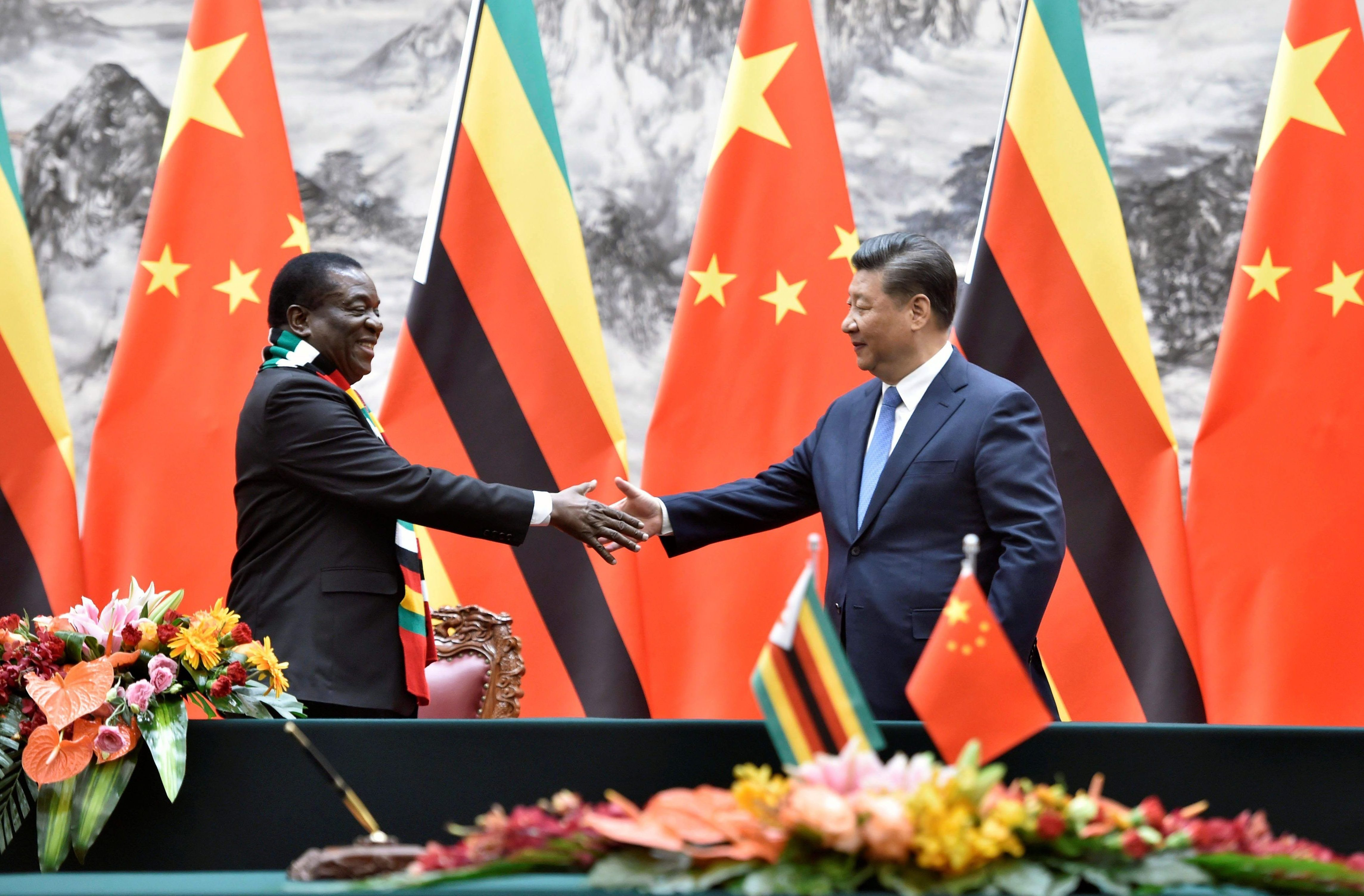 Chinese President Xi Jinping attempts to shake hands with Zimbabwean President Emmerson Mnangagwa after a signing ceremony at the Great Hall of the People in Beijing