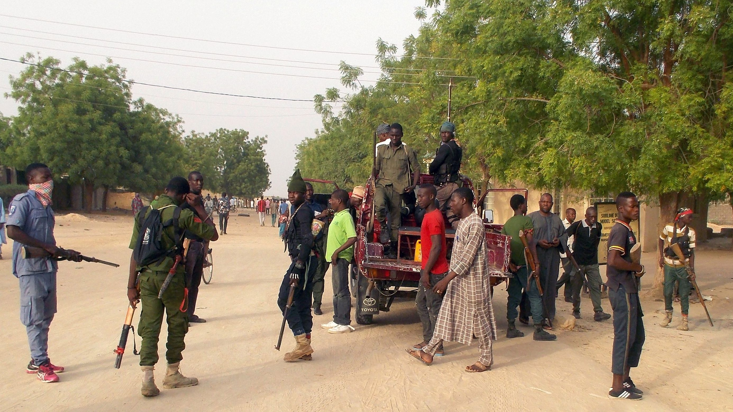 Local volunteers carrying weapons stand in the Jiddari Polo area in the northeastern city of Maiduguri, after an attack by Boko Haram militants, in Nigeria