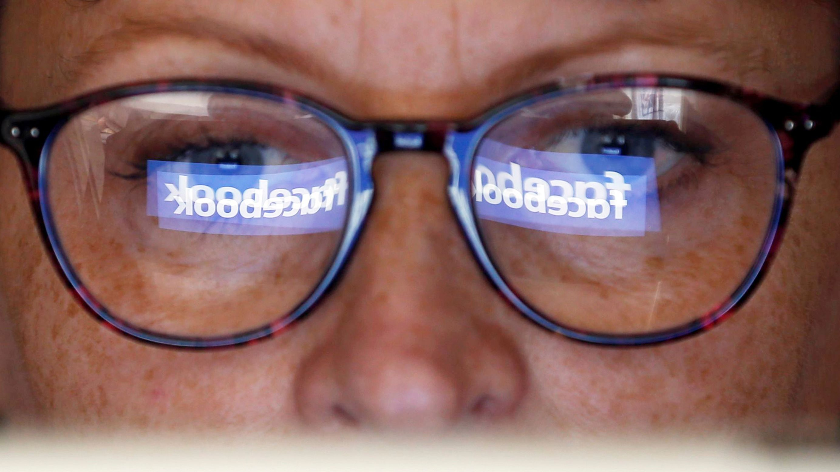 The Facebook logo is reflected on a woman's glasses in this photo illustration taken June 3, 2018. REUTERS/Regis Duvignau/Illustration - RC13DB520D70