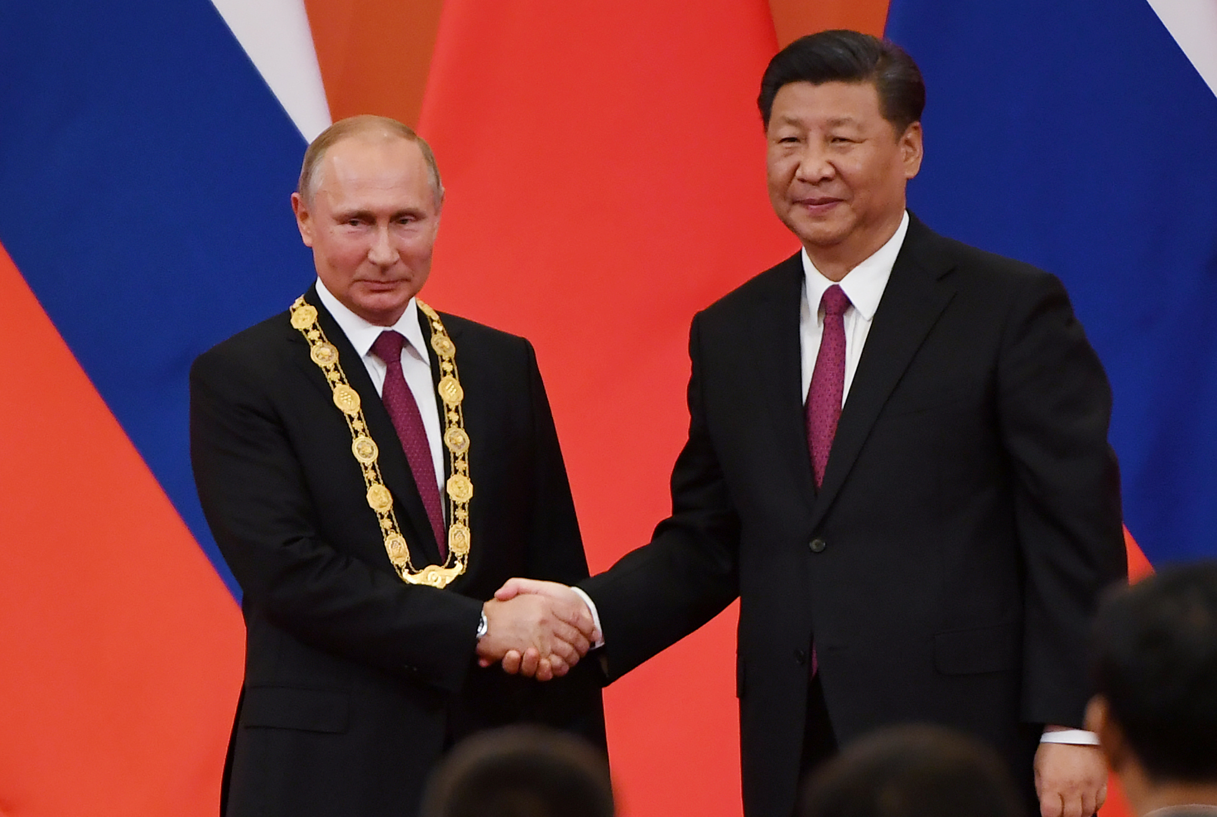 Chinese President Xi Jinping congratulates Russian President Vladimir Putin after presenting him with the Friendship Medal in the Great Hall of the People in Beijing