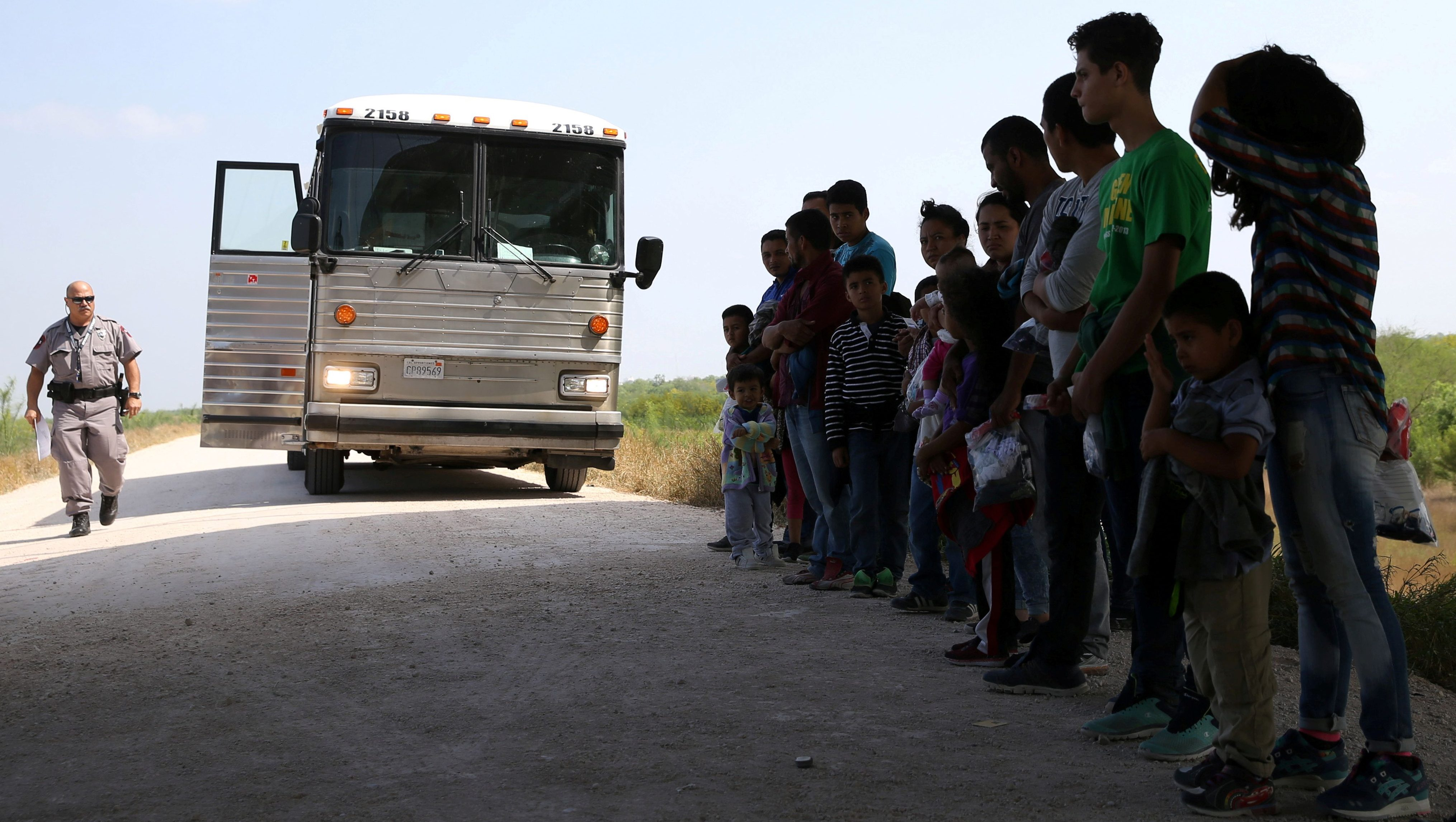 FILE PHOTO: Immigrants who turned themselves in to border patrol agents after illegally crossing the border from Mexico into the U.S. wait to be transported for processing in the Rio Grande Valley sector, near McAllen, Texas, U.S., April 2, 2018. Picture taken April 2, 2018.  REUTERS/Loren Elliott/File Photo - RC195073BC70