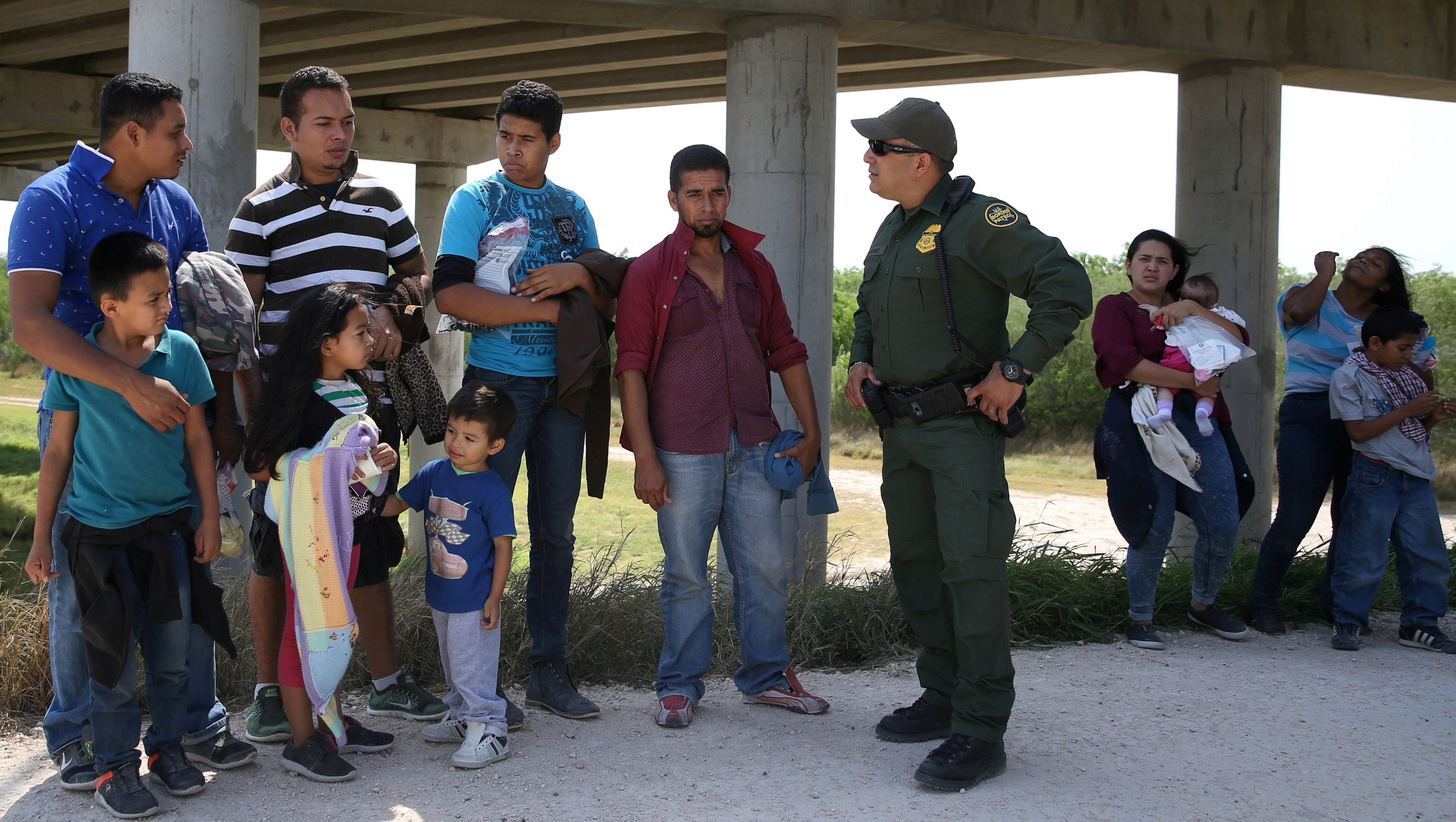 Border patrol agent with immigrants who illegally crossed the border from Mexico into the U.S.
