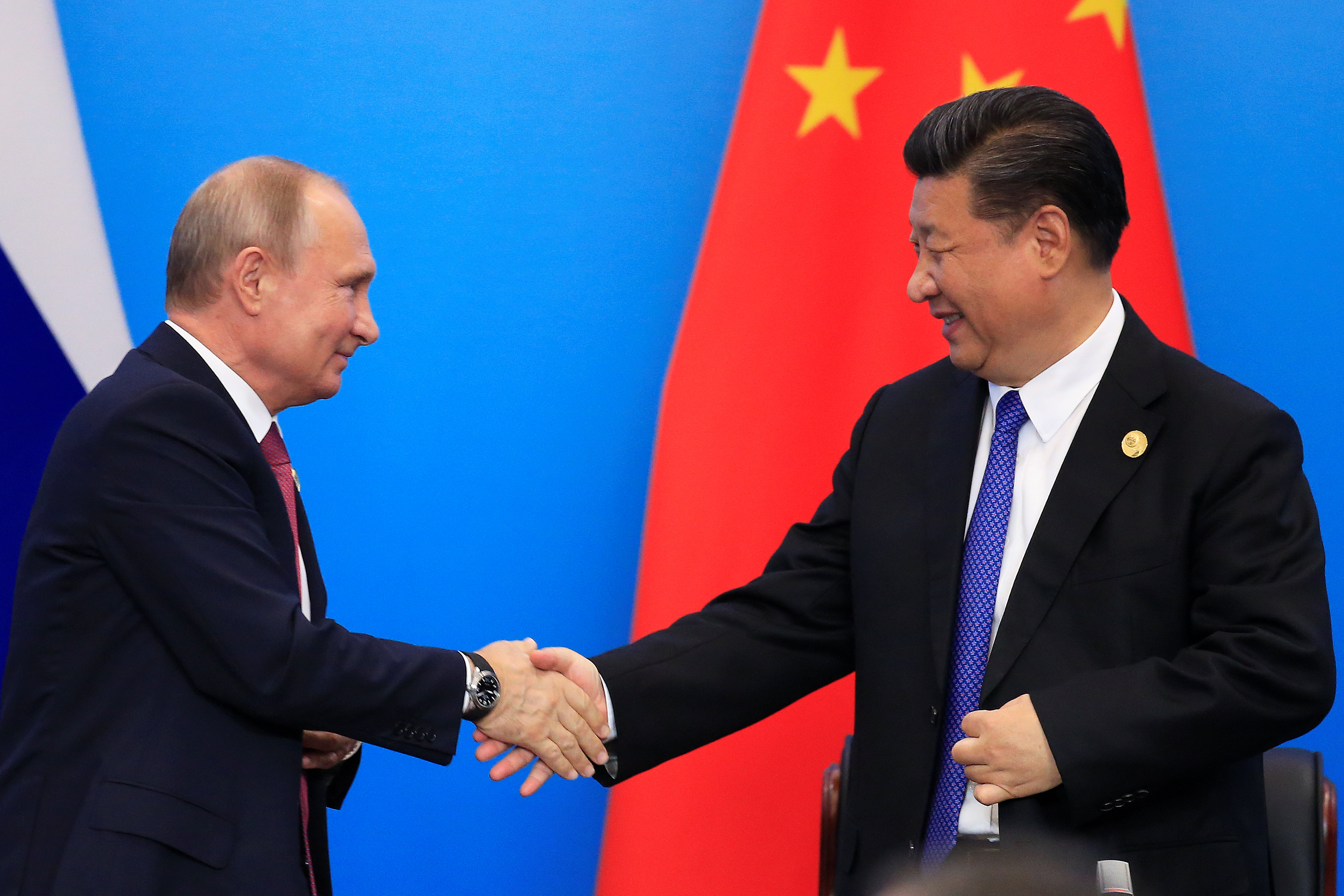 China's President Xi Jinping and Russia's President Vladimir Putin shake hands during Shanghai Cooperation Organization (SCO) summit in Qingdao, Shandong Province, China June 10, 2018.
