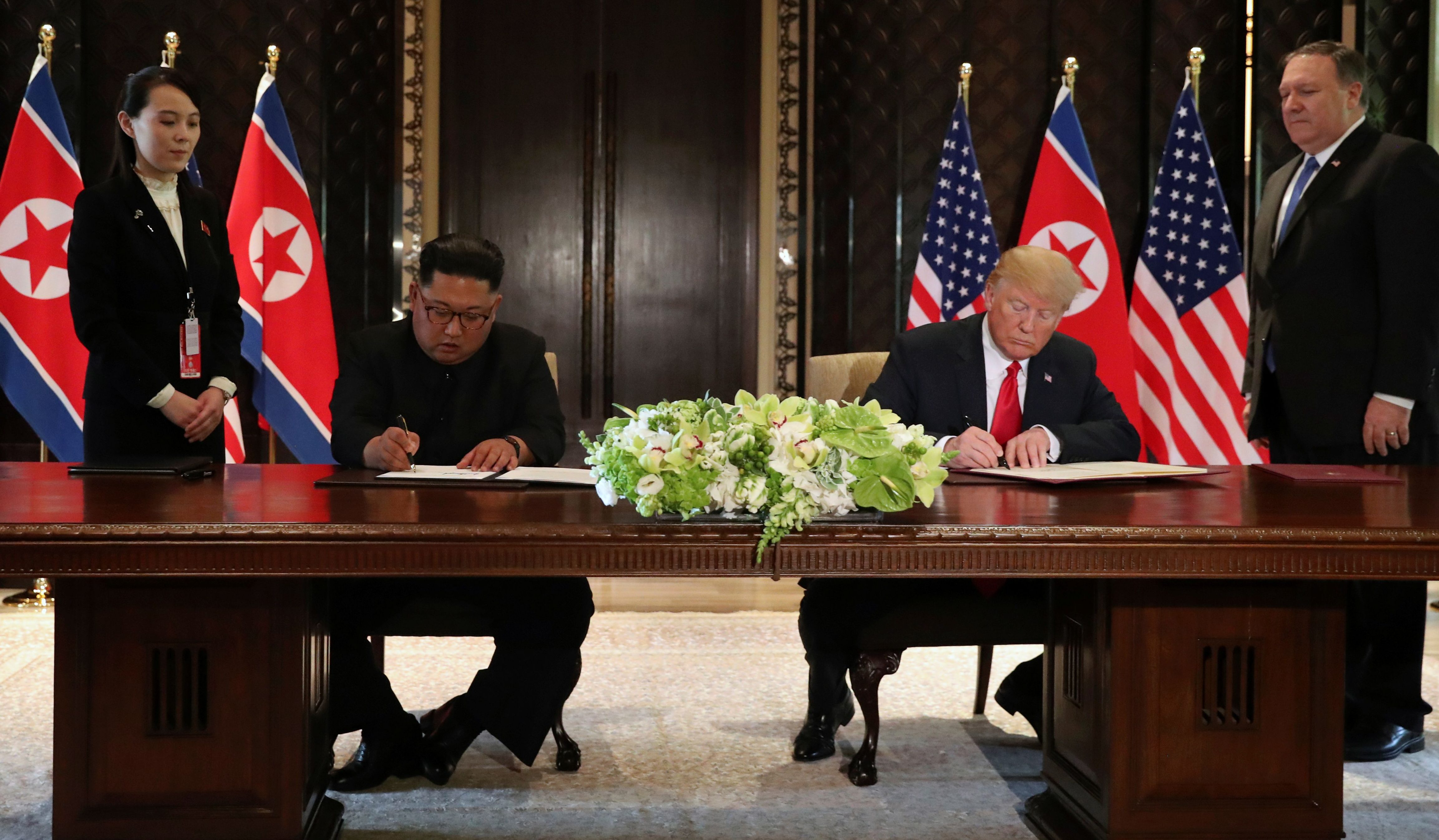 U.S. President Donald Trump and North Korea's leader Kim Jong Un sign documents that acknowledge the progress of the talks and pledge to keep momentum going, after their summit at the Capella Hotel on Sentosa island in Singapore June 12, 2018. As they are watched by Kim Yo Jong, sister of North Korean leader Kim Jong Un and U.S. Secretary of State Mike Pompeo. REUTERS/Jonathan Ernst - RC1284635E50