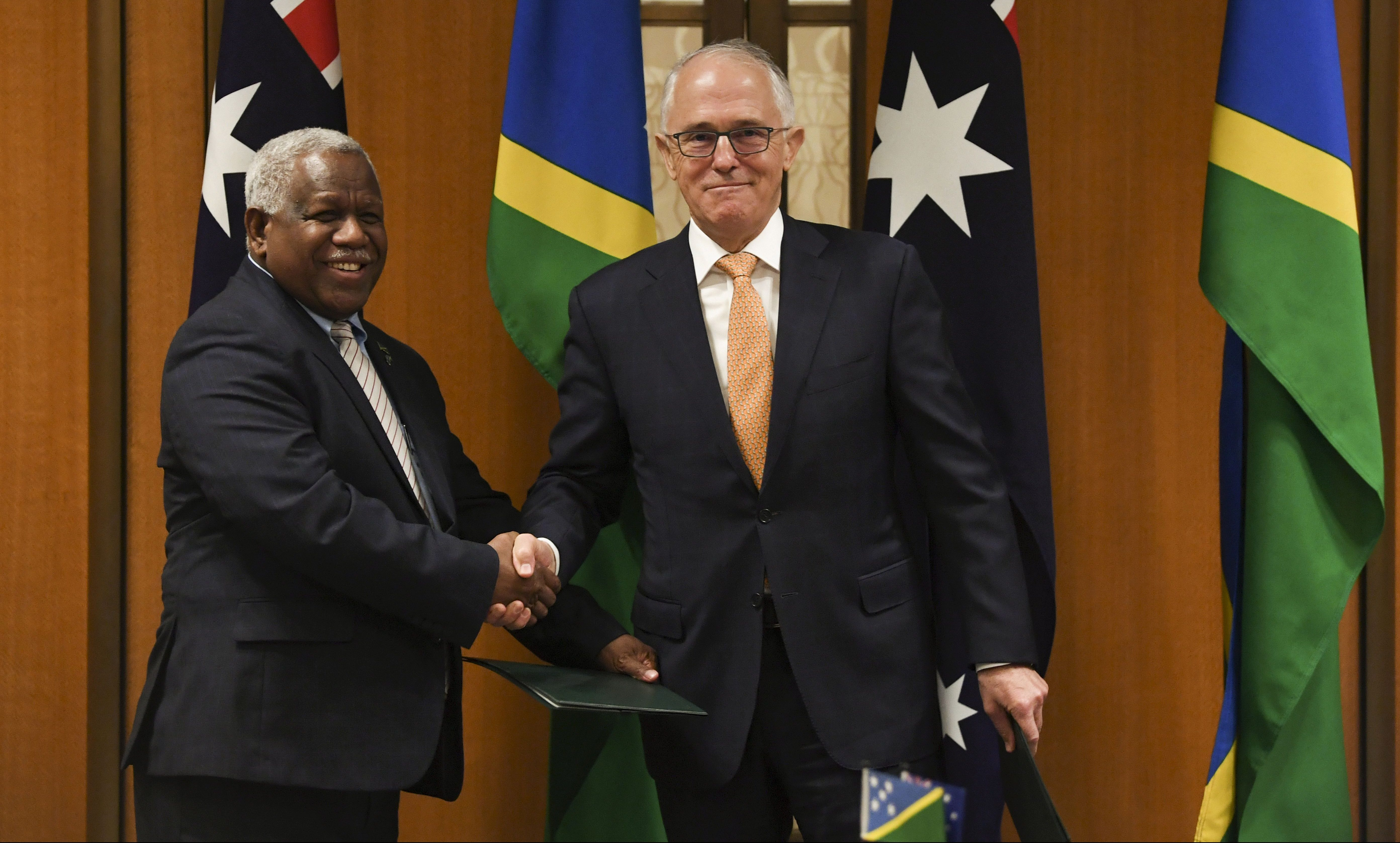 Prime Minister of the Solomon Islands Rick Houenipwela and Australian Prime Minister Malcolm Turnbull shake hands during a signing ceremony at Parliament House in Canberra