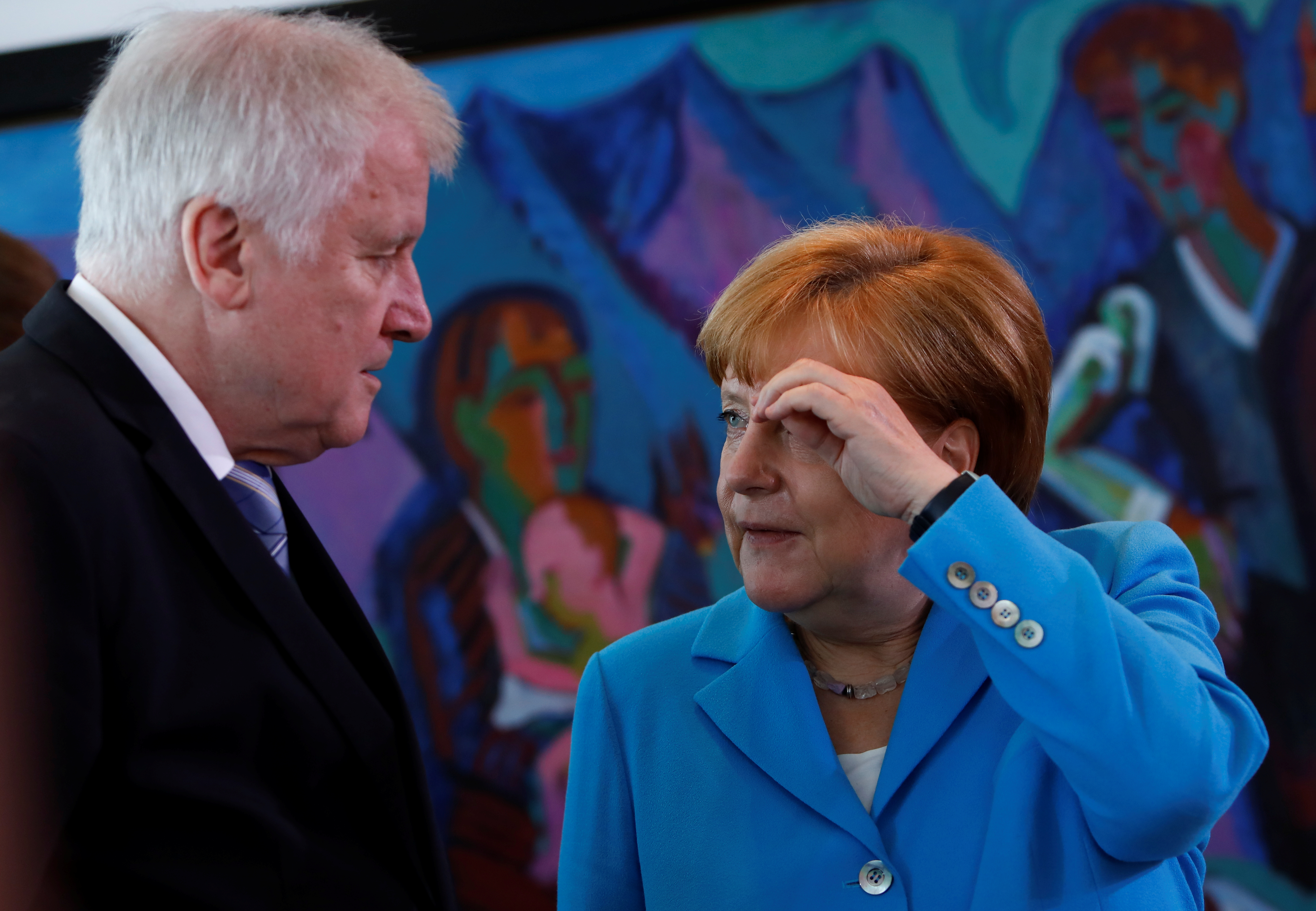 German Chancellor Angela Merkel talks to Interior Minister Horst Seehofer before the weekly cabinet meeting in Berlin, Germany, June 13, 2018. REUTERS/Michele Tantussi - RC12C114A180