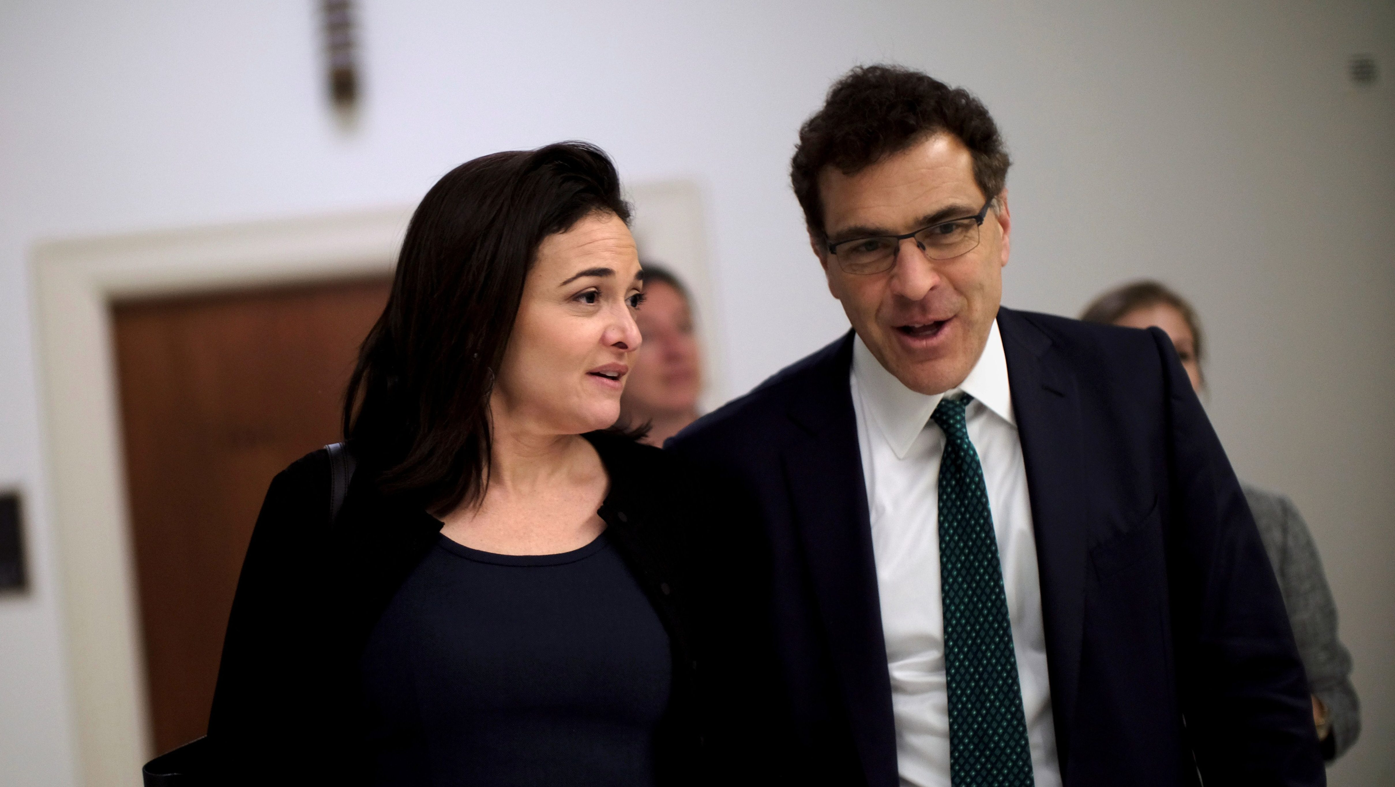 FILE PHOTO: Facebook Chief Operating Officer Sheryl Sandberg and Vice President of global communications and public policy Elliot Schrage leave after a meeting on Capitol Hill in Washington, DC, U.S., October 12, 2017.  REUTERS/James Lawler Duggan/File Photo - RC1C39B45C00