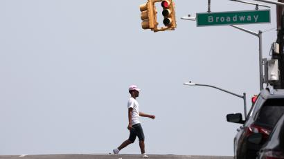 A man crosses West 145th Street during very hot weather in the Washington Heights section of Manhattan in New York City
