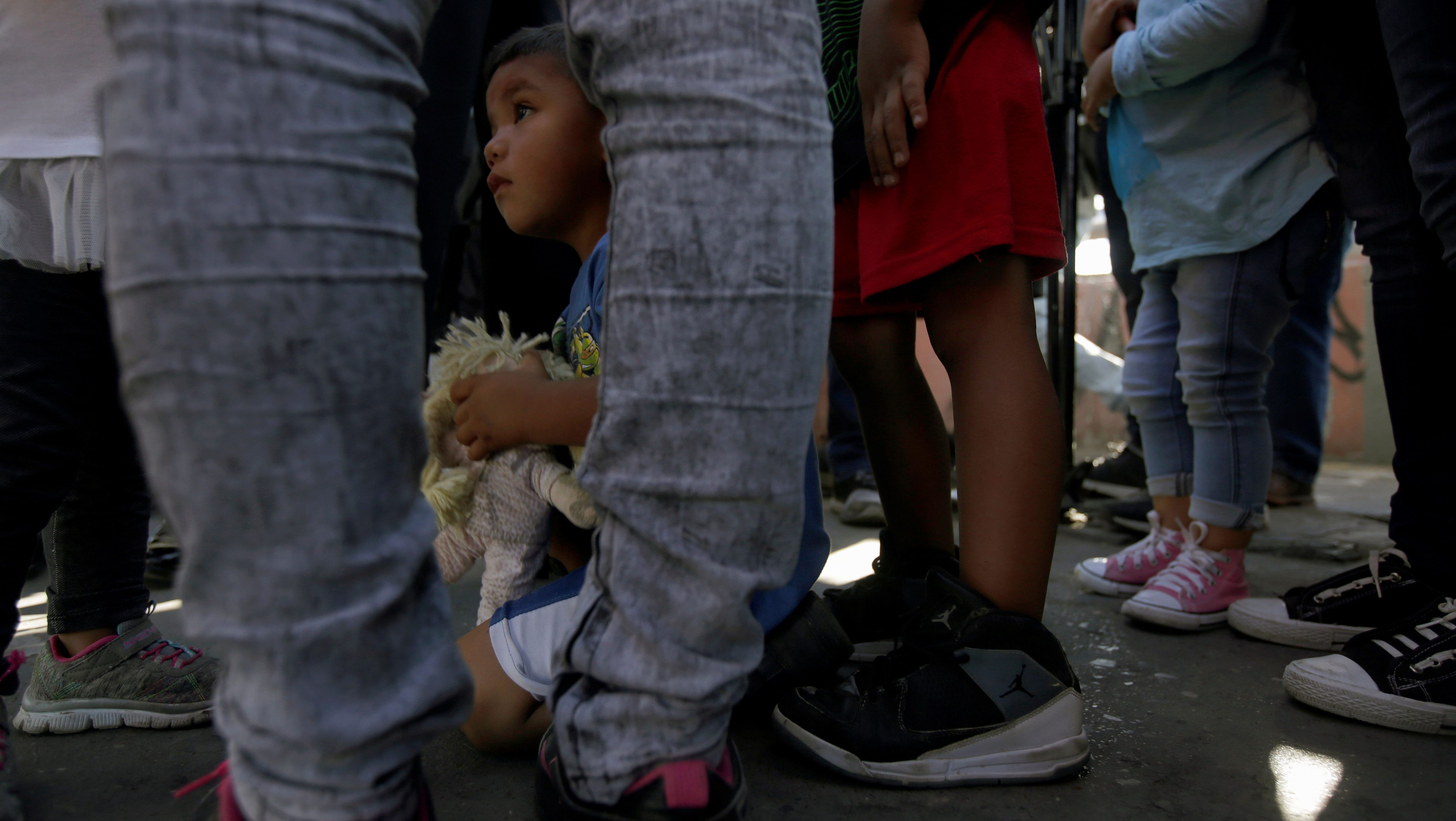 Migrant families fleeing from violence, wait to enter the United States to meet officers of the U.S. Customs and Border Protection to apply for asylum
