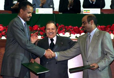 Algerian President Abdelaziz Bouteflika (C) stands between Eritrean President Isayas Afewerki (L) who shakes hands with Ethiopian Prime Minister Meles Zenawi (R) after signing peace agreements December 12, 2000. Ethiopia and Eritrea formally ended their two-year border war after months of mediation by the Organisation of African Unity (OAU), the United Nations and the United States. - PBEAHULFNBJ