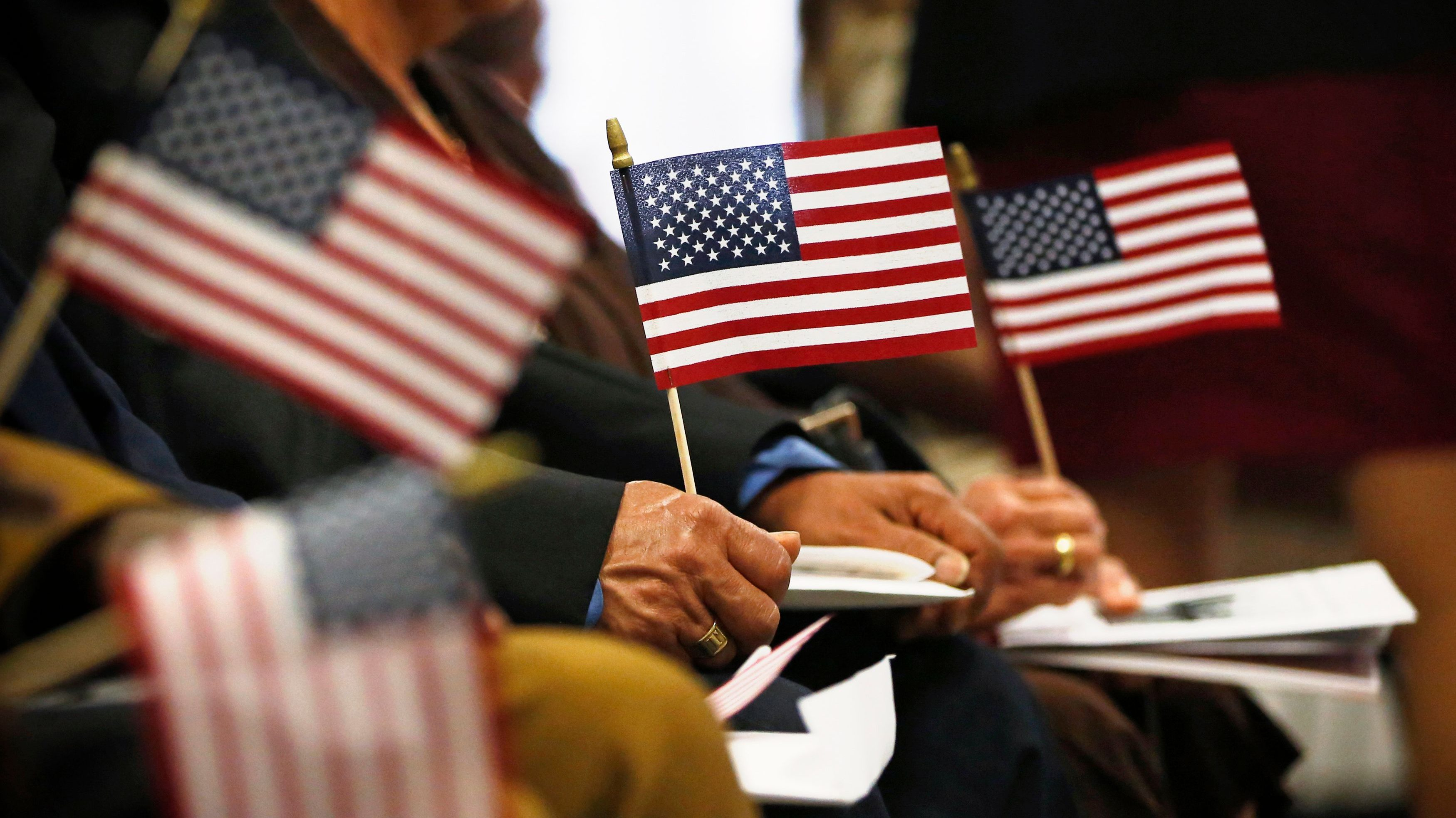 """Immigrants hold U.S. flags during their naturalization ceremony to become new citizens of the U.S. in New York, April 17, 2013. President Barack Obama on Tuesday embraced a sweeping overhaul of the nation's immigration system put forward by a bipartisan group of senators, saying it was """"largely consistent"""" with his own principles for immigration reform. REUTERS/Brendan McDermid (UNITED STATES  - Tags: SOCIETY IMMIGRATION POLITICS) - GM1E94I09A801"""