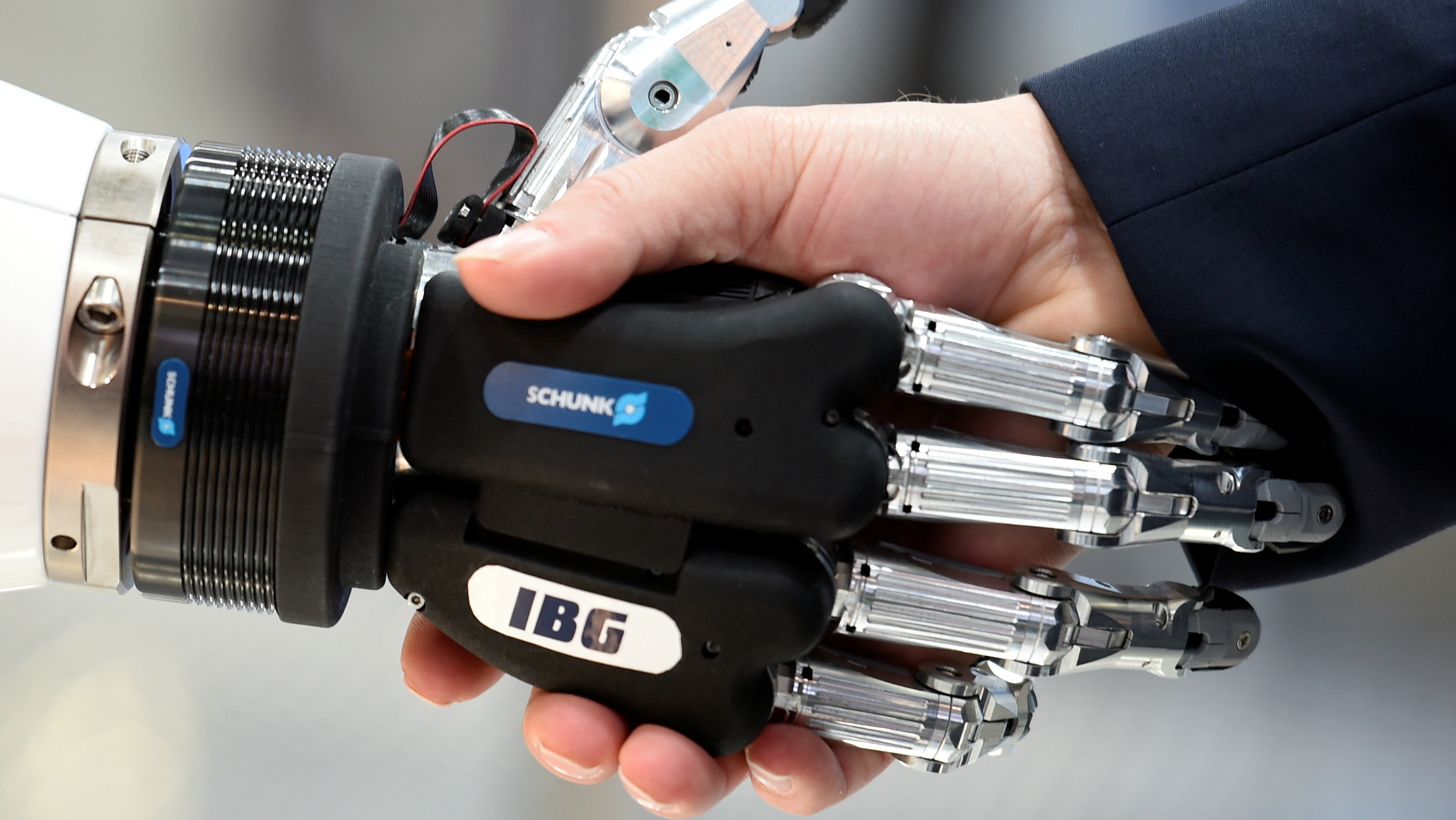 A visitor shakes hands with a humanoid robot.