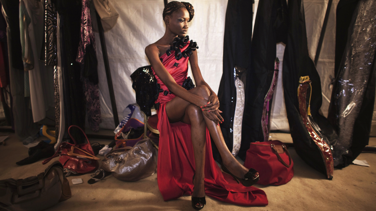 Model Nafissatou Gningue wears a creation by Egyptian designer Tito backstage during the 10th annual Dakar Fashion Week June 16, 2012. Picture taken June 16, 2012. REUTERS/Finbarr O'Reilly (SENEGAL - Tags: FASHION ENTERTAINMENT SOCIETY) - GM2E86H1Q8M01