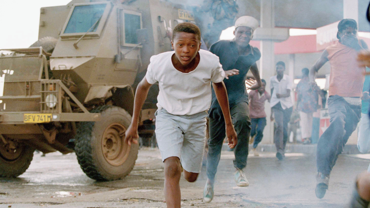 Township residents flee from tear gas fired by police during clashes between ANC and Zulu Inkatha Freedom Party supporters near a Zulu worker's hostel in Soweto, South Africa, March 29, 1994. Tensions ran high a day after ANC security guards opened fire on protesting Zulus outside the ANC headquarters in downtown Johannesburg on Monday killing nine. The IFP are opposed to next months all race general elections. (AP Photo/Joao Silva)