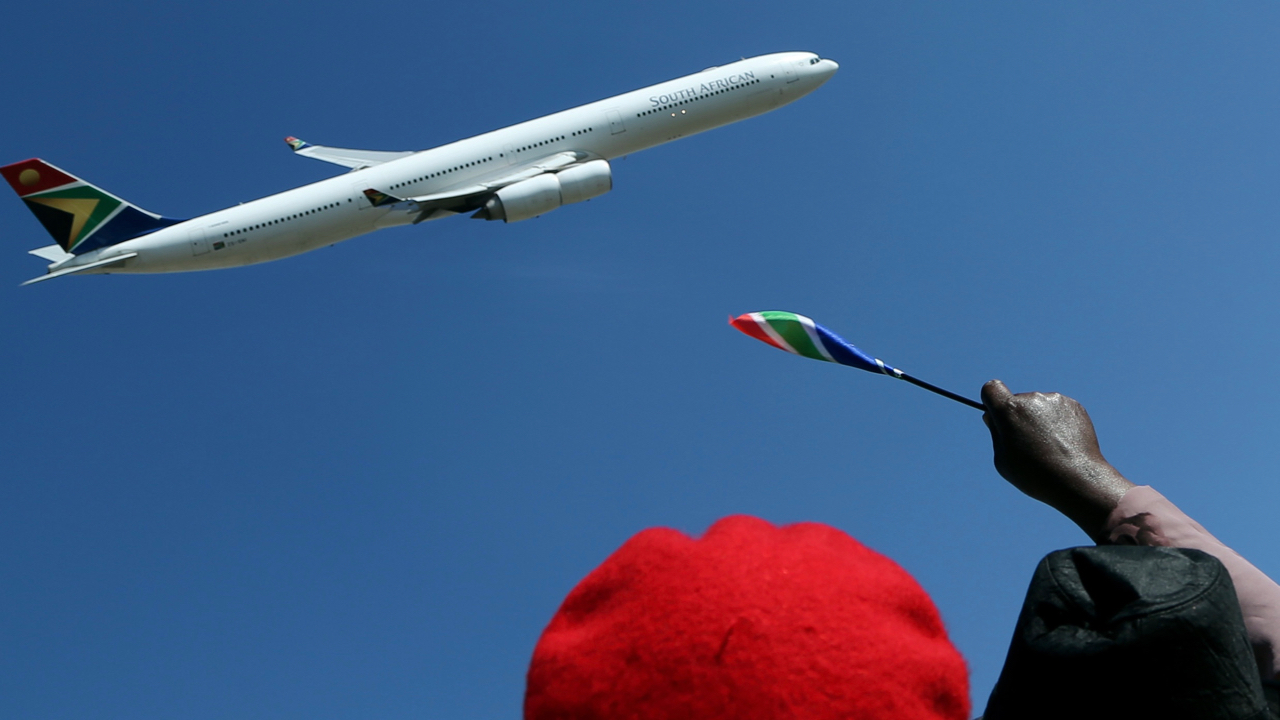 Ruling party supporters wave for a South African Airways Airbus flyby during the inauguration of the Union Building in Pretoria, South Africa, Saturday, May 24, 2014. The ruling African National Congress won elections for a fifth time since the first democratic vote in 1994. (AP Photo/Themba Hadebe)