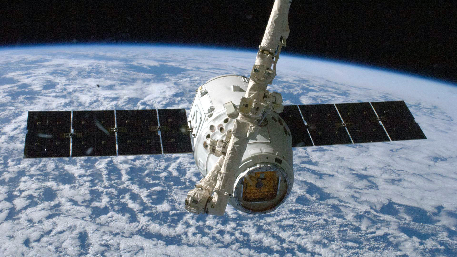 The SpaceX Dragon commercial cargo craft is grappled by the International Space Station's Canadarm2 robotic arm.