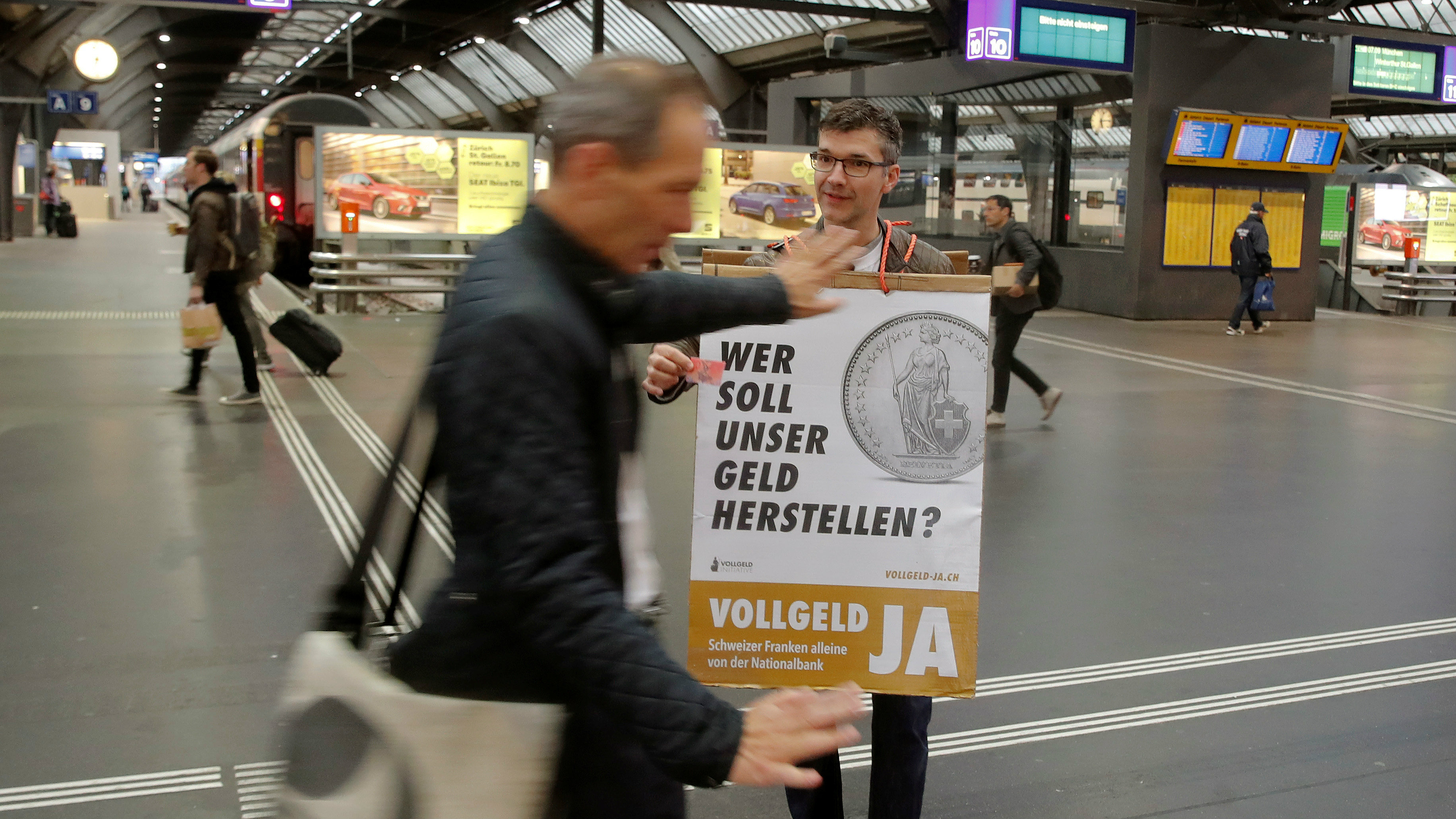"""A member of the sovereign money initiative, a referendum campaign that would abolish traditional bank lending and allow only money created by the Swiss National Bank (SNB), offers flyers to travellers at the central railway station in Zurich, Switzerland May 3, 2018. The poster reads, """"Who should produce our money? Sovereign money yes - Swiss francs from National Bank only""""."""