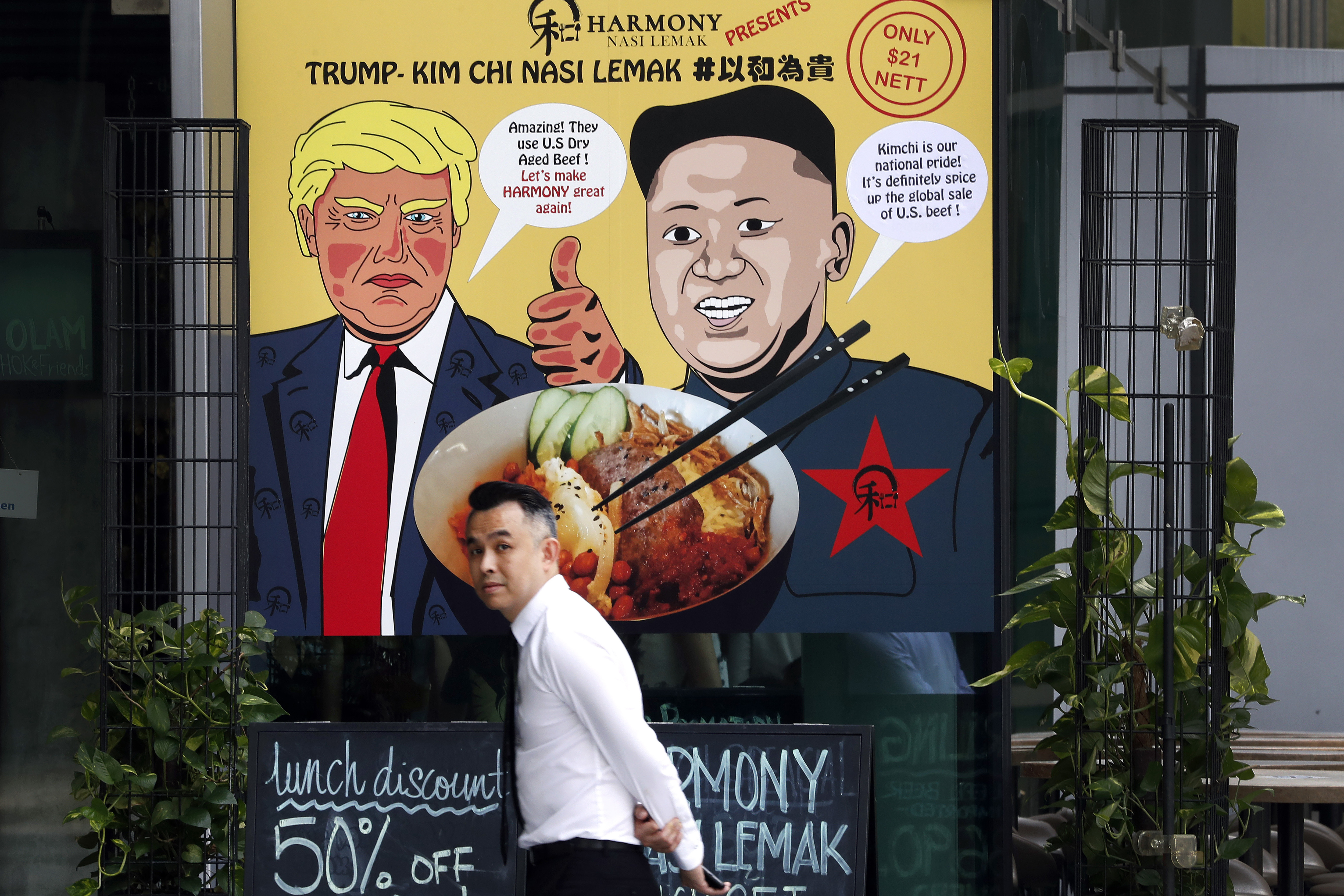 """A man walks past an advertisement board of cartoon caricatures of U.S. President Donald Trump and North Korean leader Kim Jong Un which are supposed to be the inspiration behind a local dish, the """"Trump-Kim Chi Nasi Lemak"""" at a mall on Thursday, June 7, 2018, in Singapore. Trump and Kim will meet at a luxury resort in Singapore next week for nuclear talks, the White House said Tuesday. (AP Photo/Wong Maye-E)"""