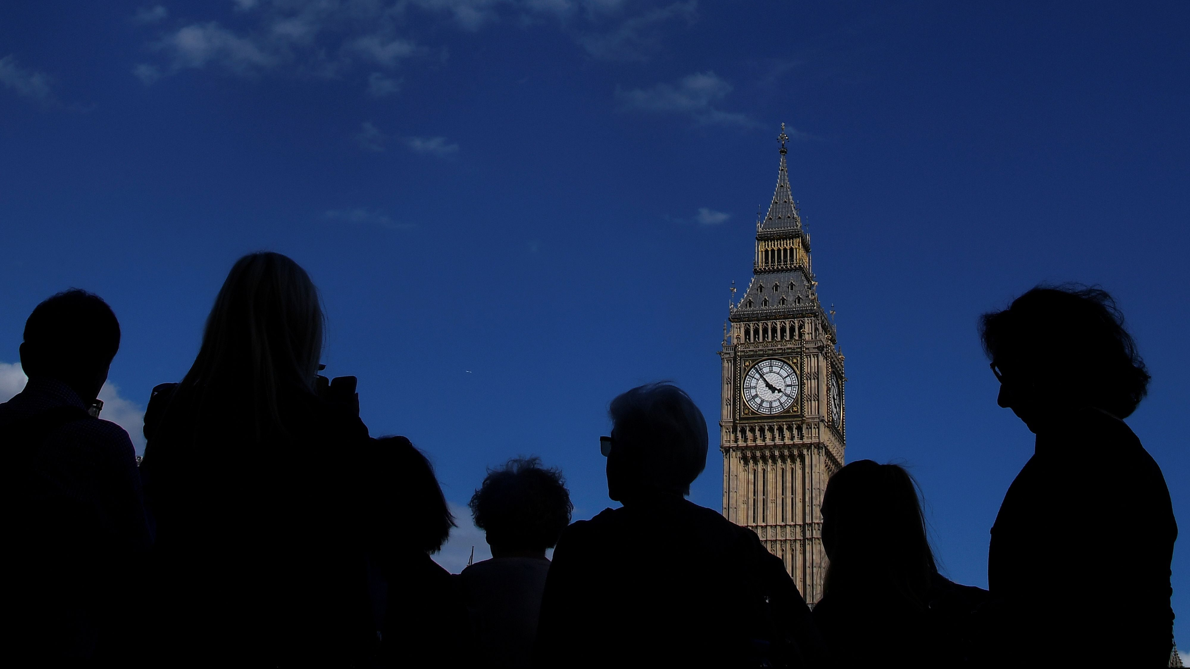 Tourists view the Elizabeth Tower, which houses the Great Clock and the 'Big Ben' bell, at the Houses of Parliament, in central London