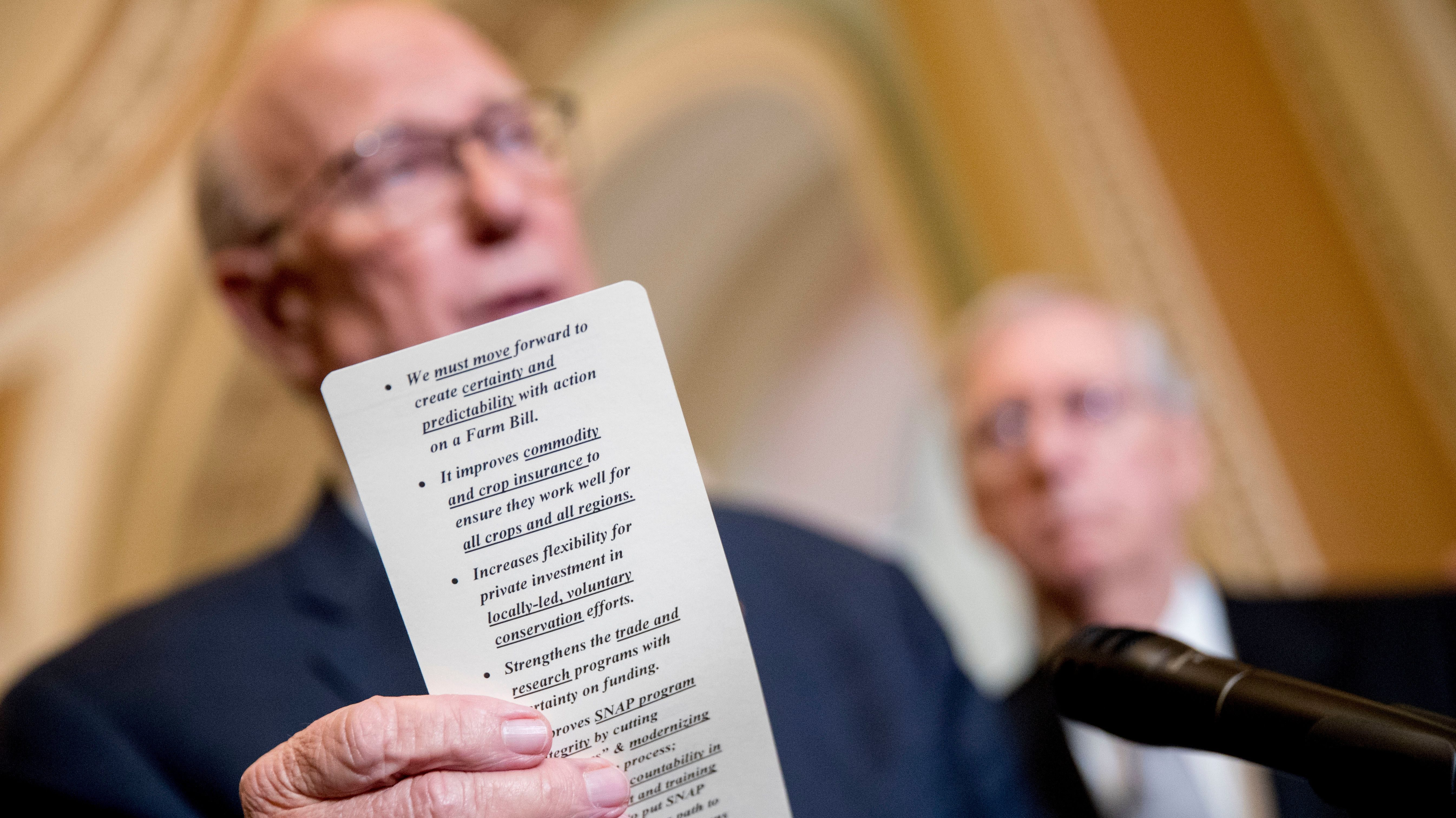 Senator Pat Roberts, accompanied by Senate Majority Leader Mitch McConnell, reads from notes on the farm bill as he speaks with reporters on Capitol Hill, on June 26, 2018.