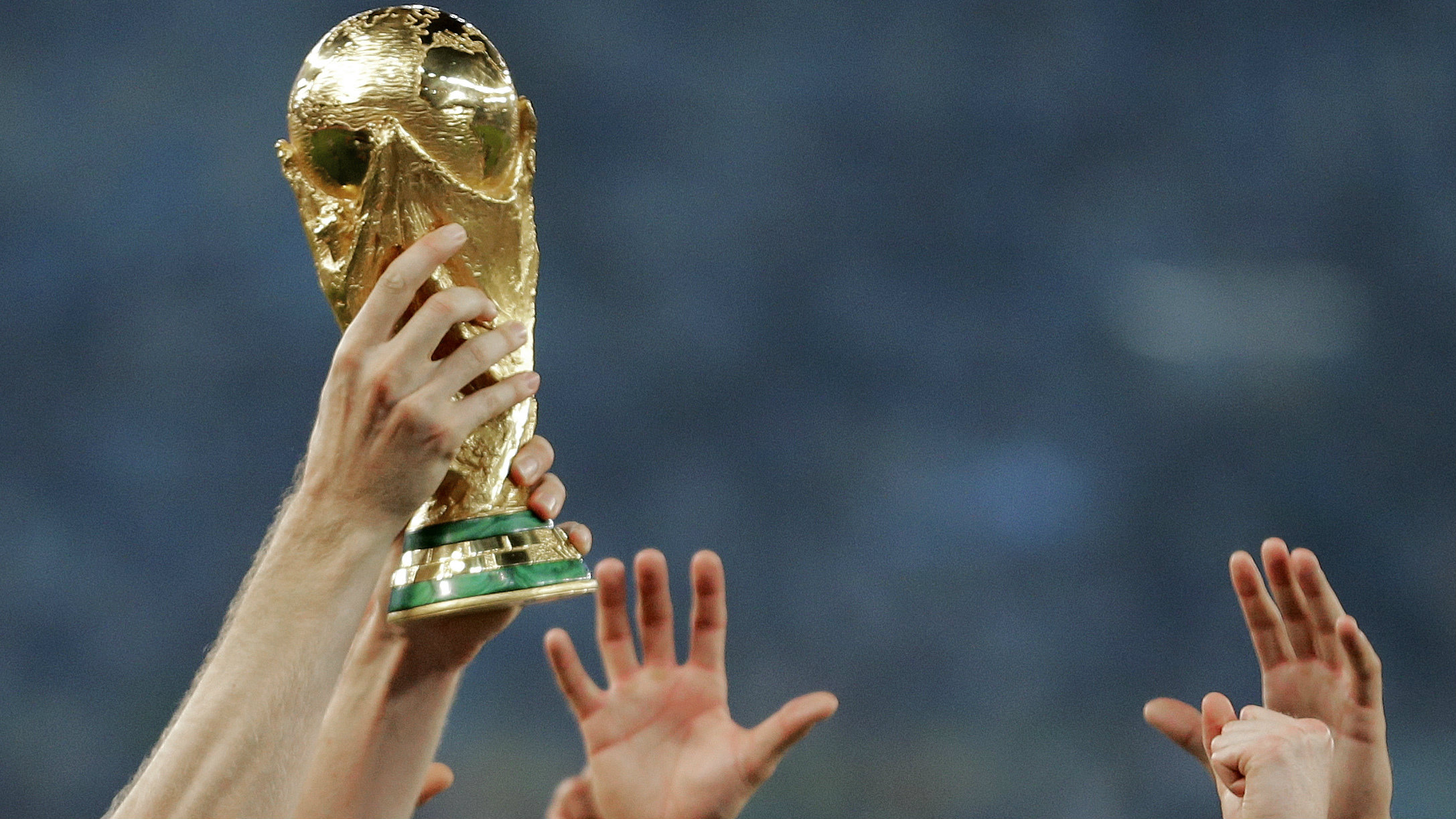 In this Sunday, July 13, 2014 file photo, German players reach out to touch the trophy after the World Cup final soccer match between Germany and Argentina at the Maracana Stadium in Rio de Janeiro, Brazil. Morocco will bid to host the 2026 World Cup, giving a joint bid from North America some competition. The Morocco Football Federation announced its intention to bid on Friday, Aug. 11, 2017 the deadline for countries to express their interest.