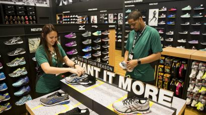 Two sales associates lace up shoes at a DICK'S Sporting Goods