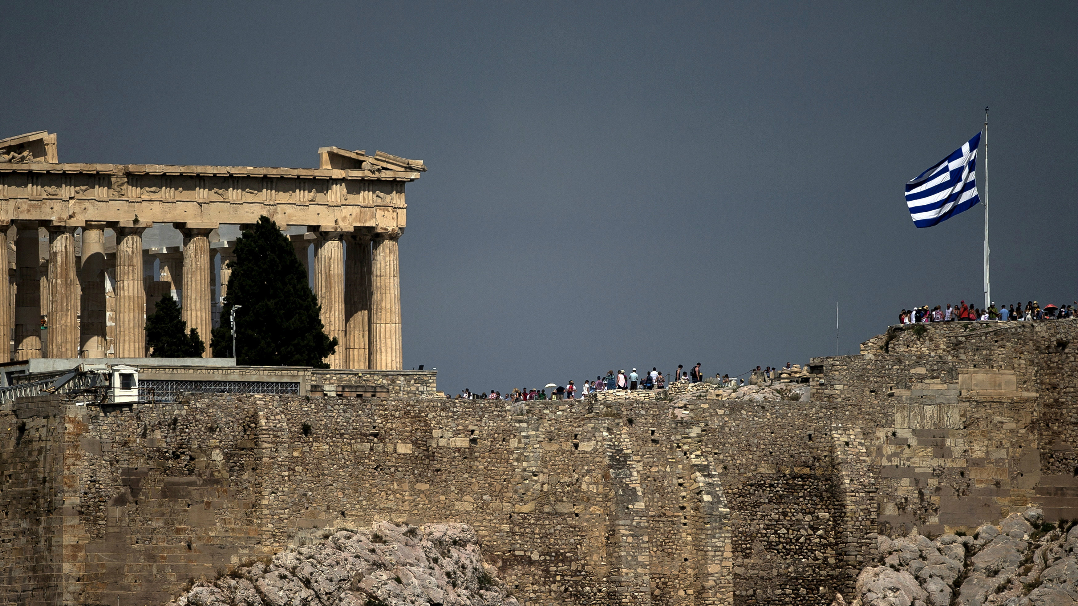 A Greek flag flutters in front of the ancient Parthenon temple atop the Acropolis hill